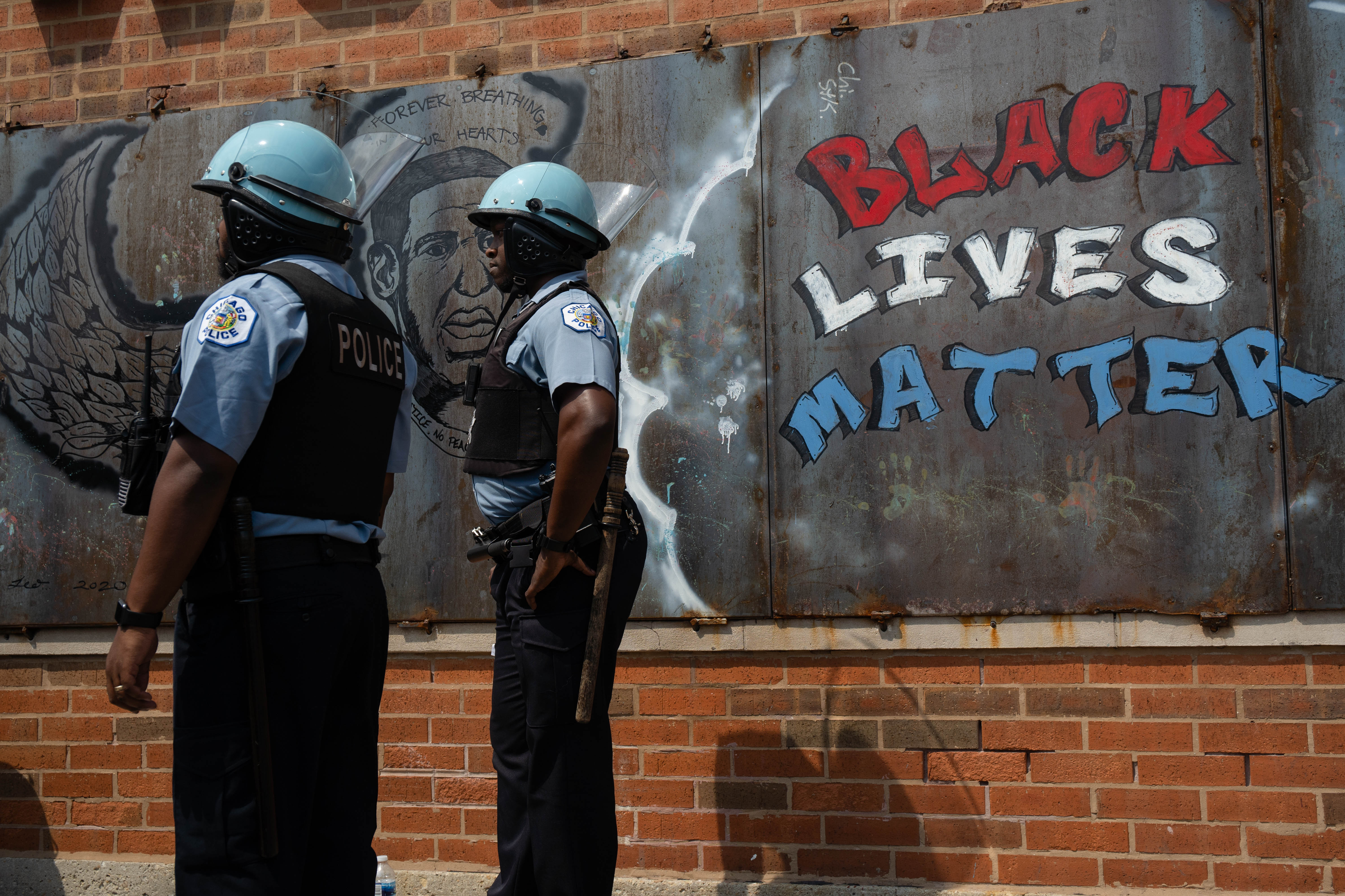 Police officers stand beside a mural for George Floyd in Bronzeville during an anti-police brutality protest Saturday afternoon, Aug. 15, 2020.