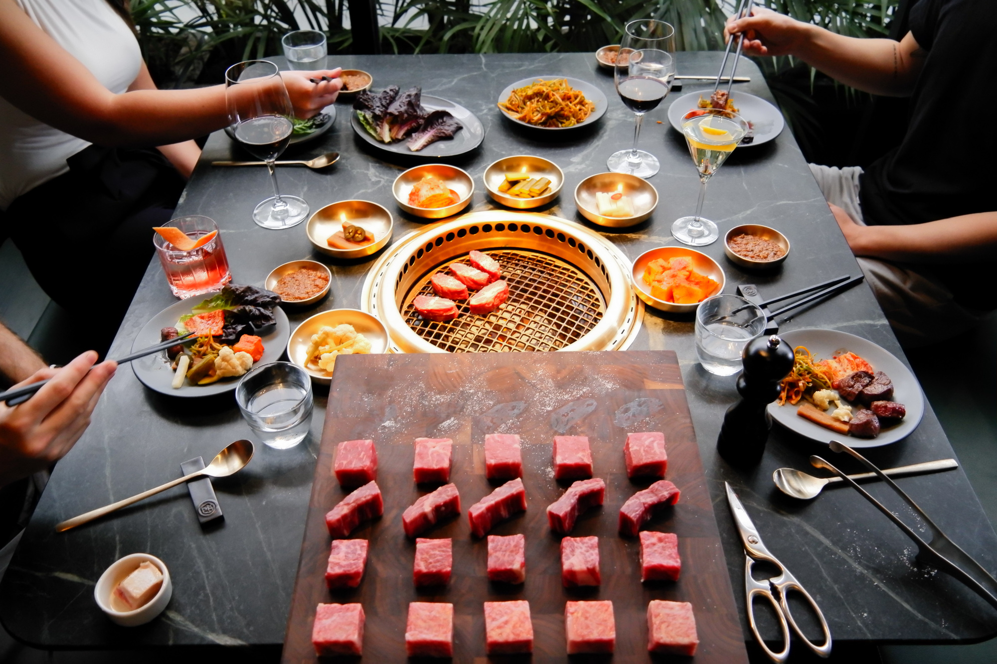 A table with an inset grill surrounded by banchan