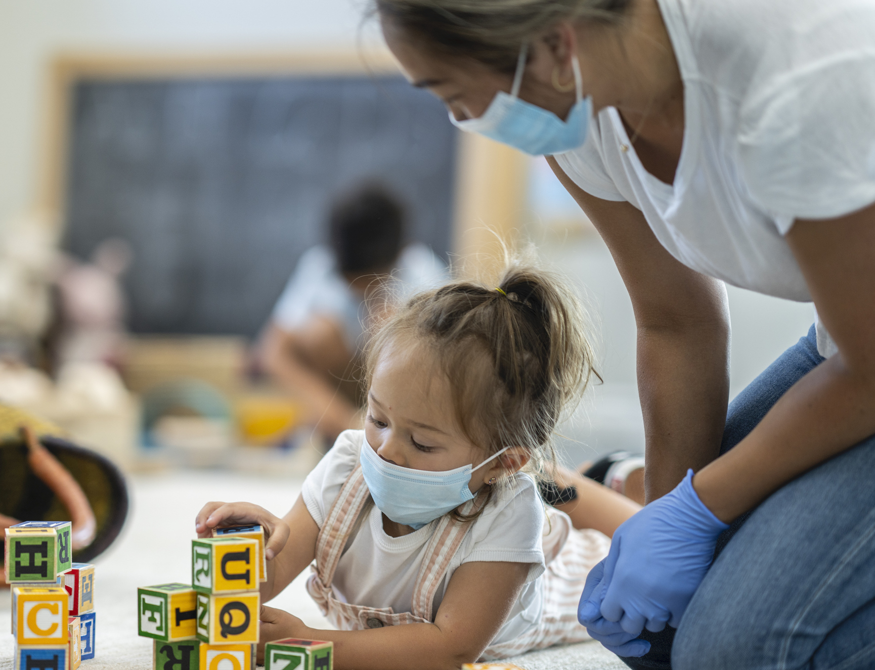 Young girl in mask plays with blocks while masked and gloved woman watches