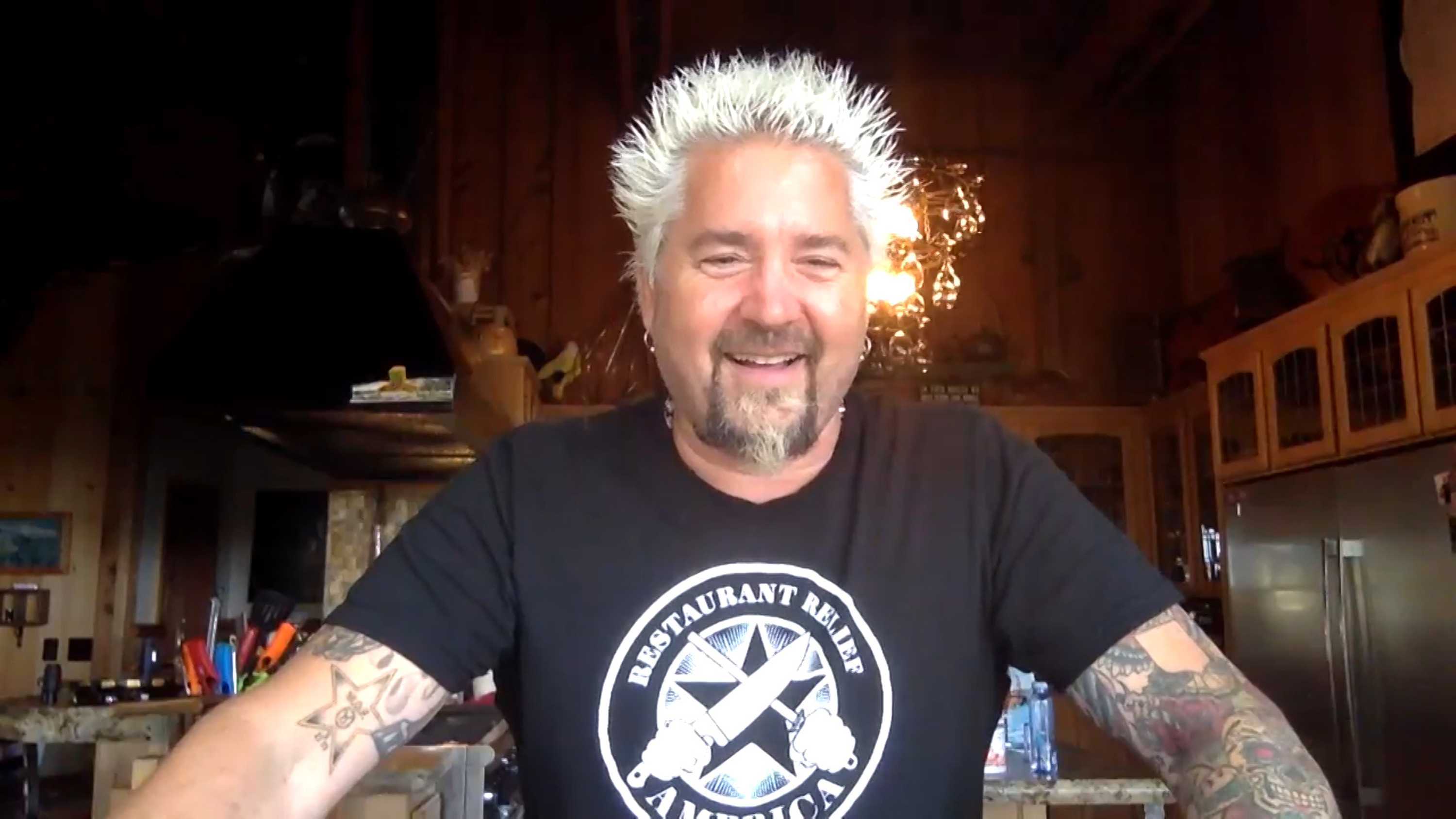 Chef Guy Fieri wearing a dark short-sleeve shirt and smiling into the camera