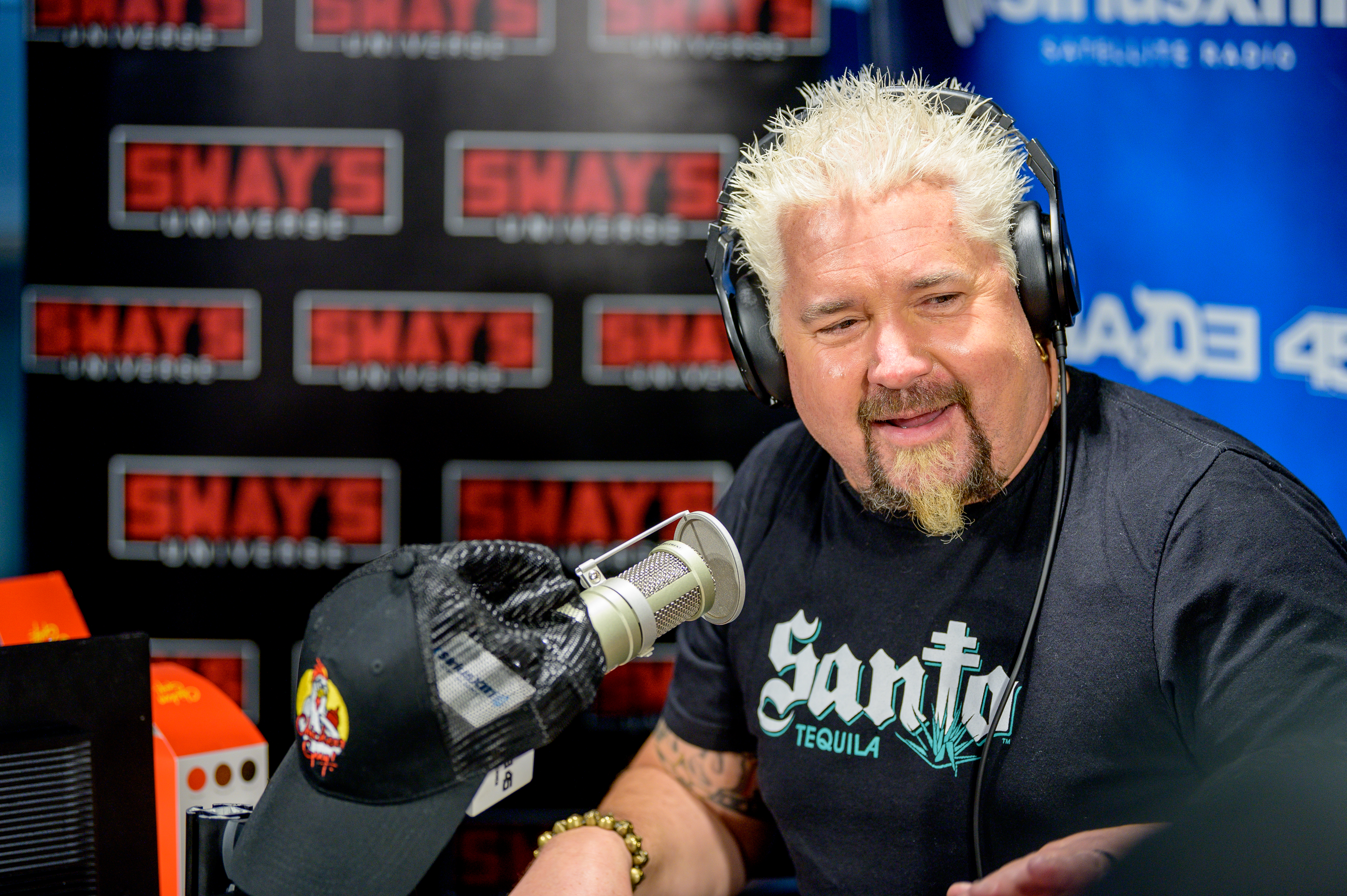 With his signature spiked blond hair and goatee, Guy Fieri wears headphones and a dark blue t-shirt while recording a radio interview.