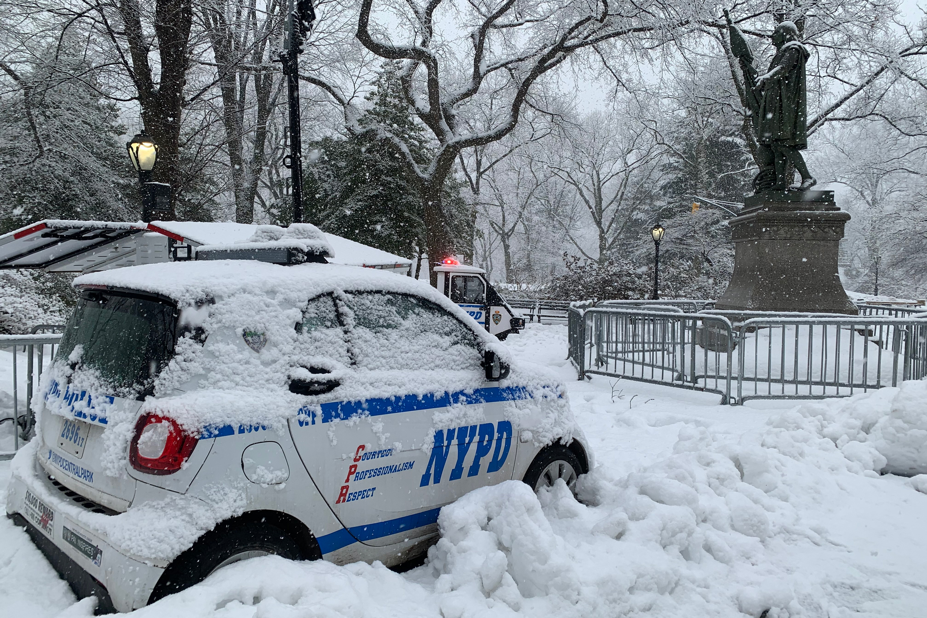 Multiple NYPD officers guard a statue of Christopher Columbus in Central Park during a snowstorm, Feb. 7, 2021.