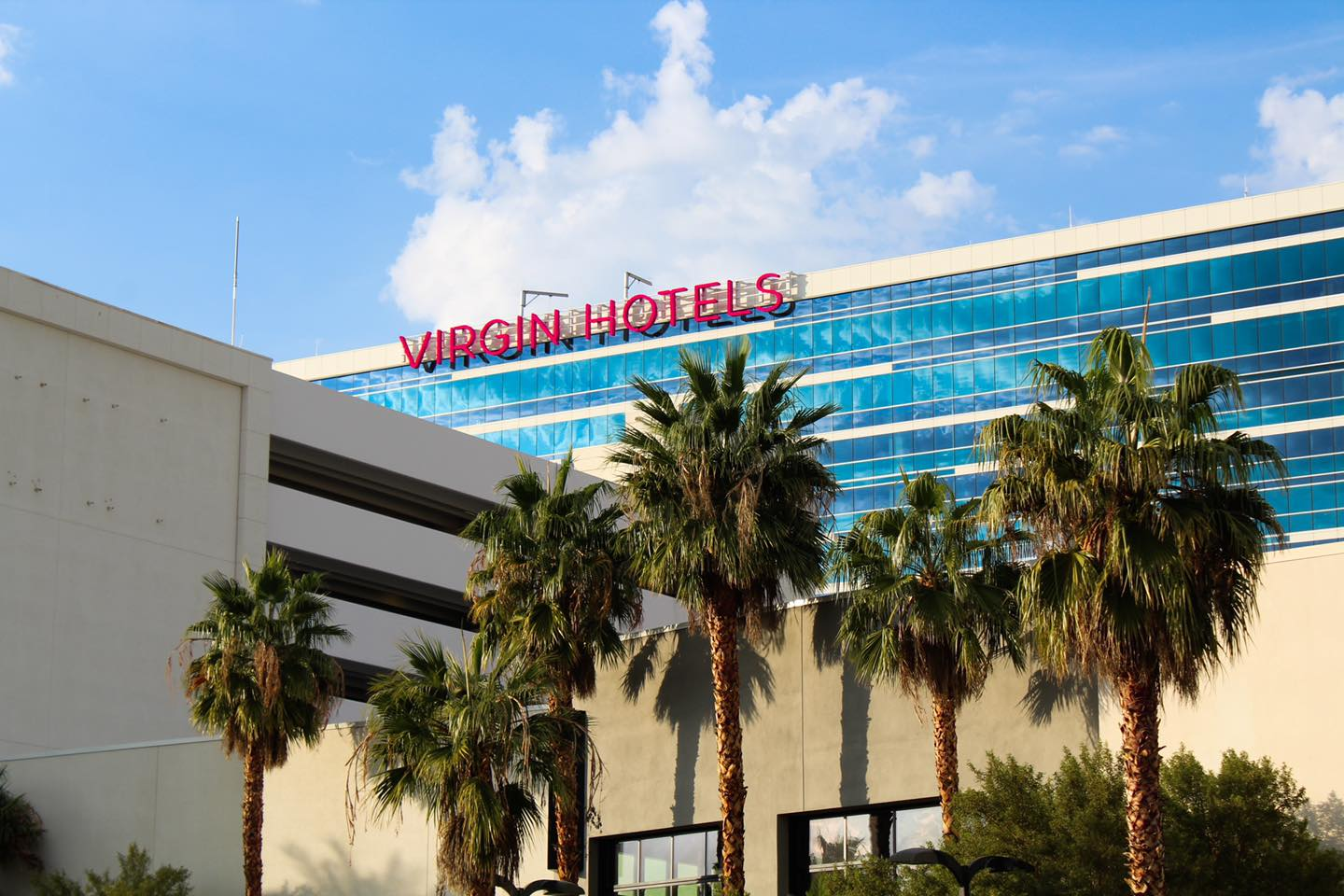 The exterior of a hotel with a red sign on top, blue windows, palm trees, and a parking garage