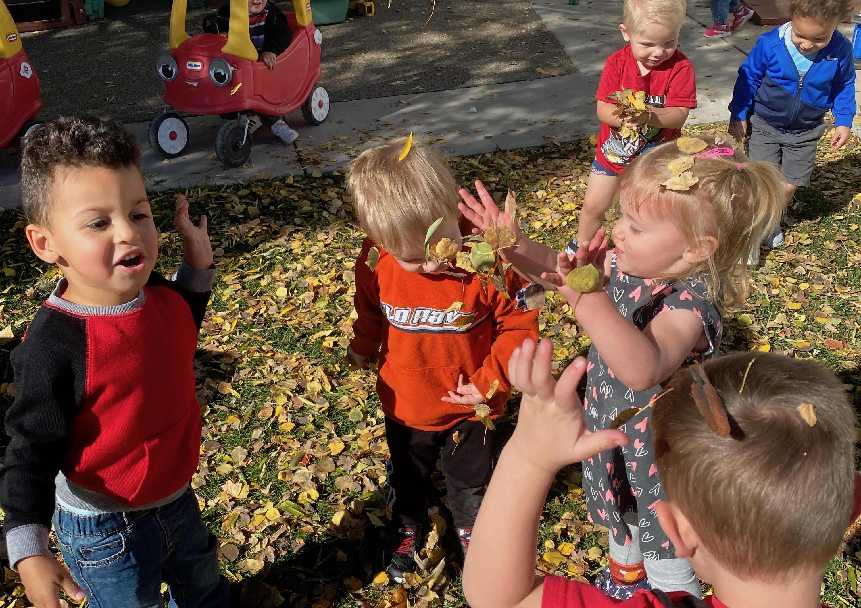 Six preschool children play in fall leaves