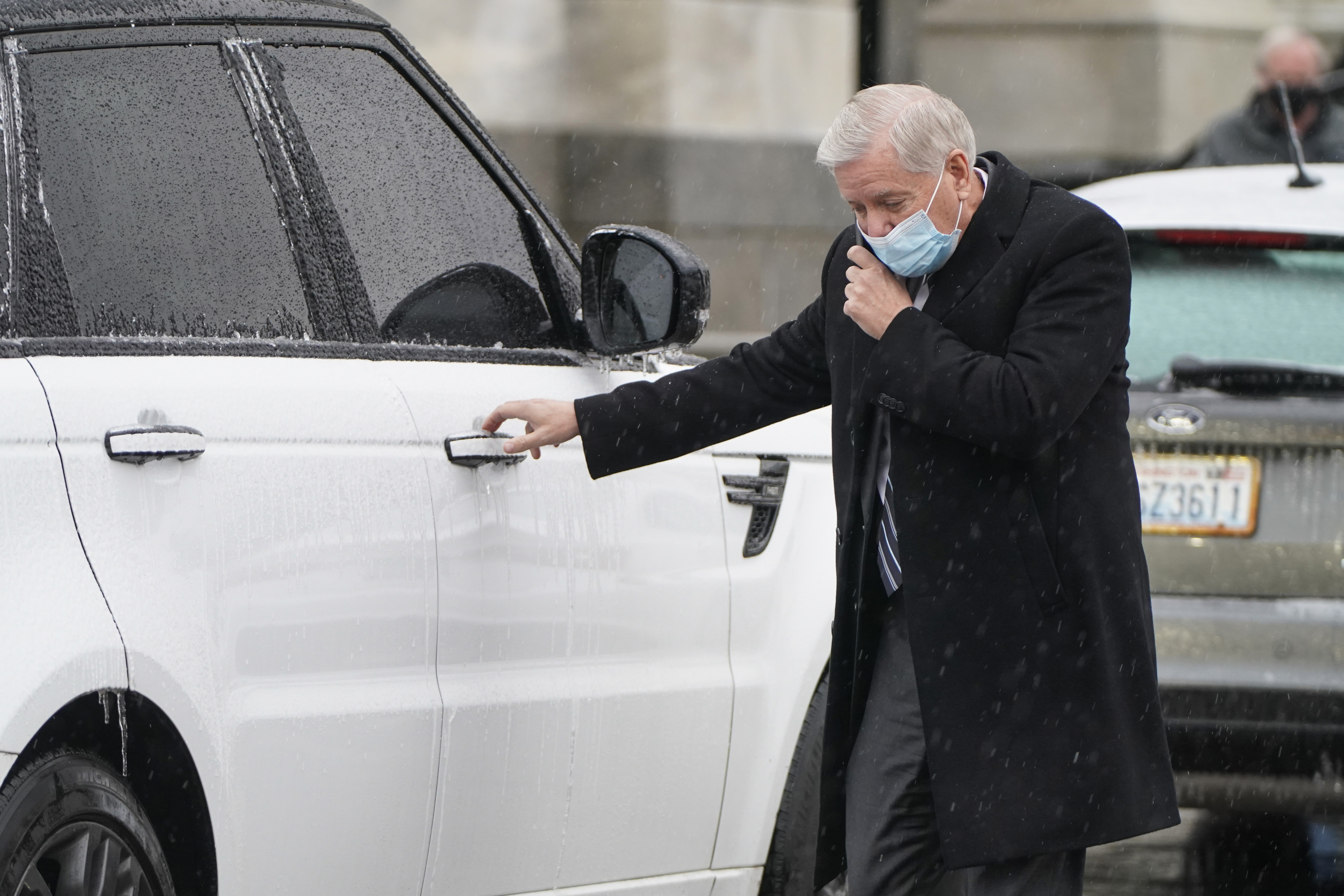 Lindsey Graham  reaches for the door of his car.