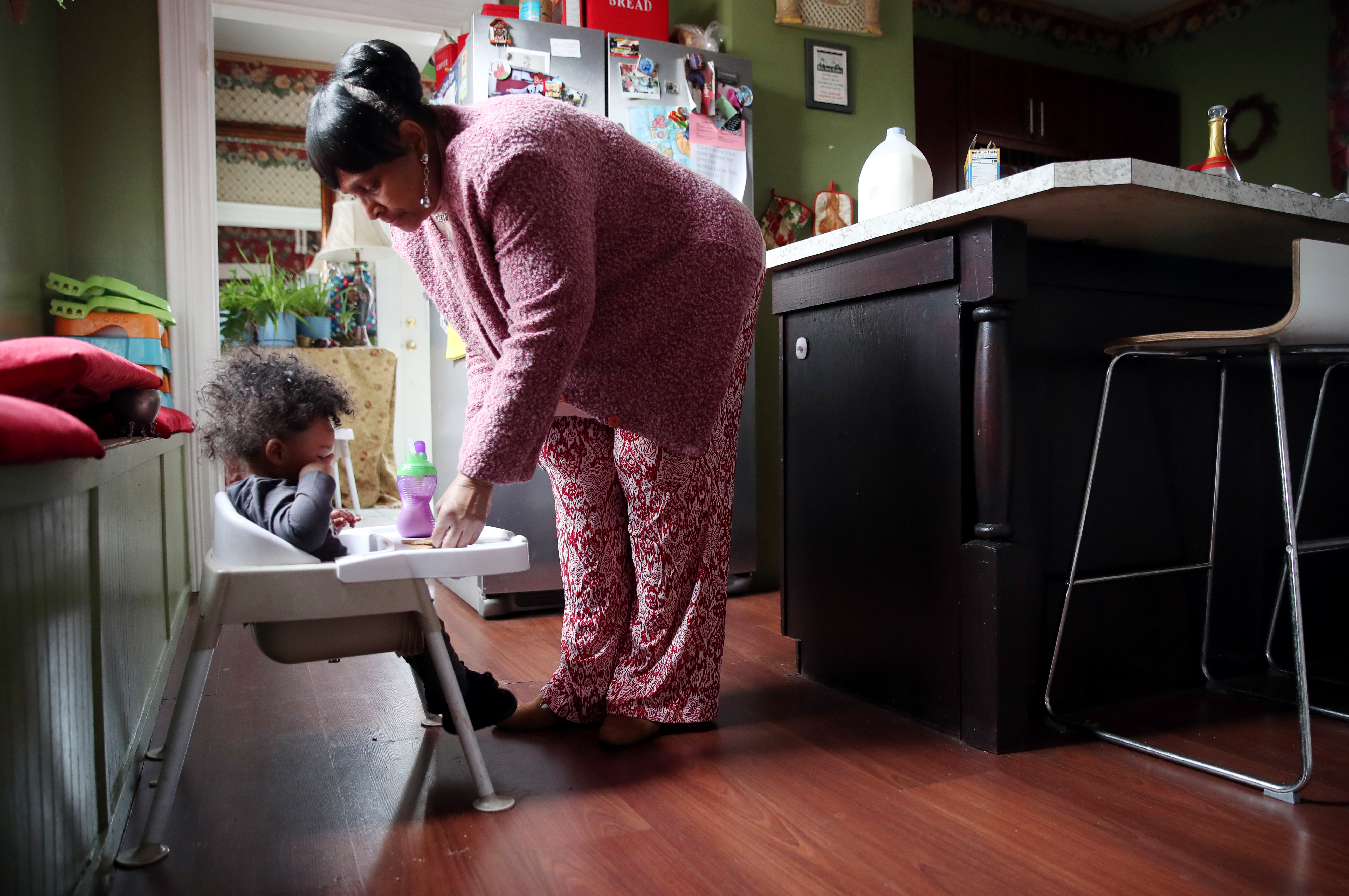 A child care provider stands over a baby sitting in a small feeding chair.