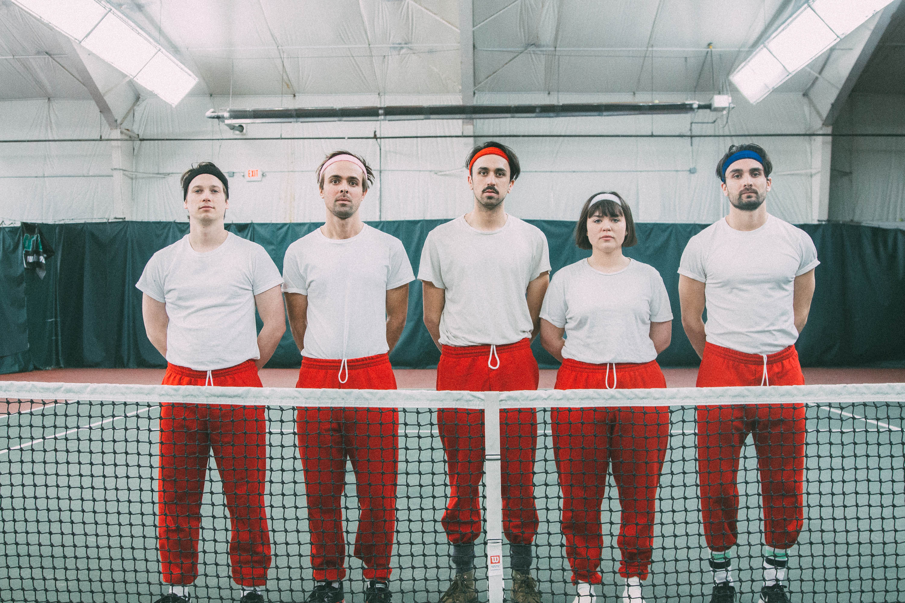 The members of Fever Dolls wear matching outfits — white shirts and red pants — on a tennis court.
