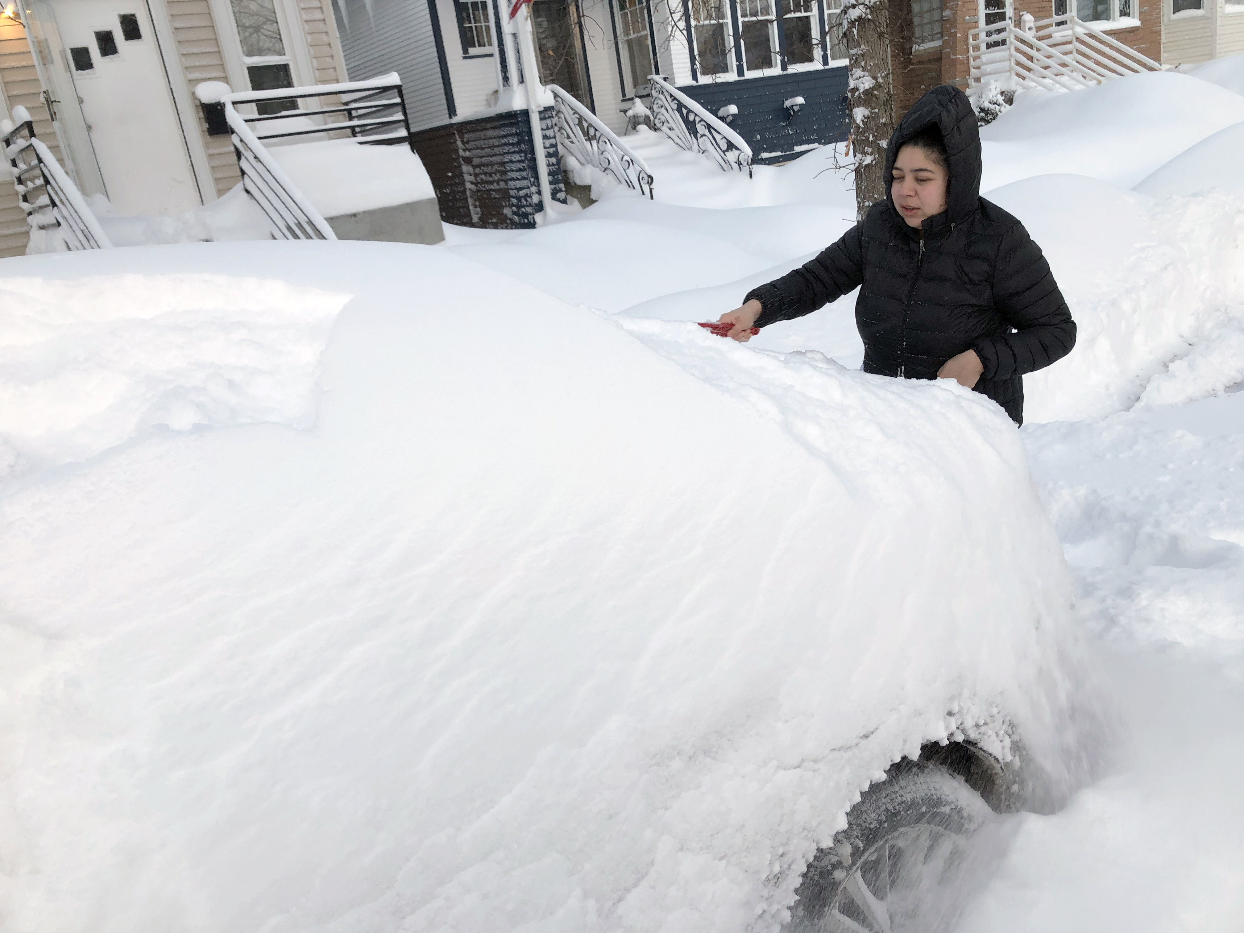 Jennifer Vazquez tries to clear snow off of her car Tuesday morning in Portage Park.