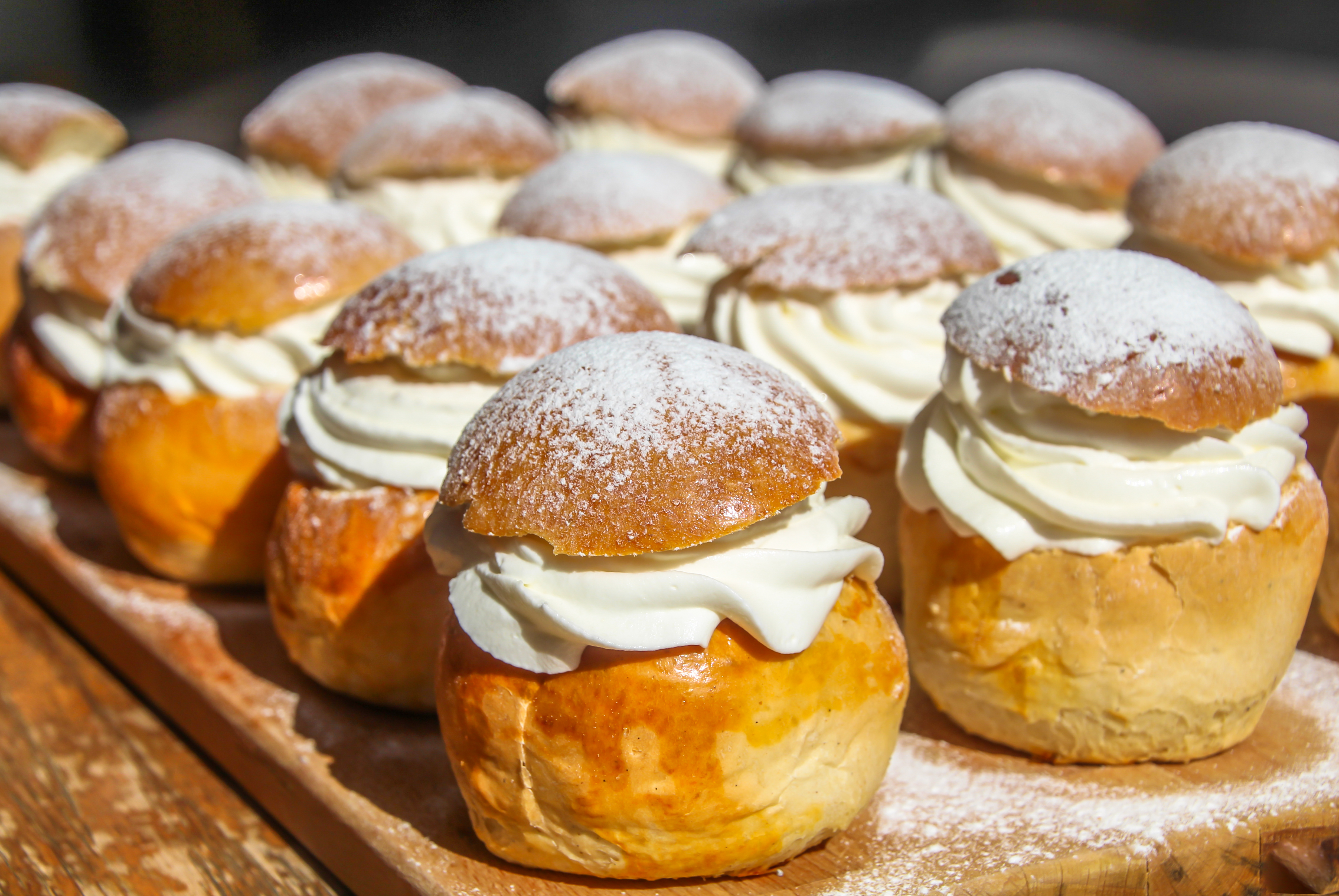 A cutting board with rows of semlor pastries, cream filled and dusted with powdered sugar.