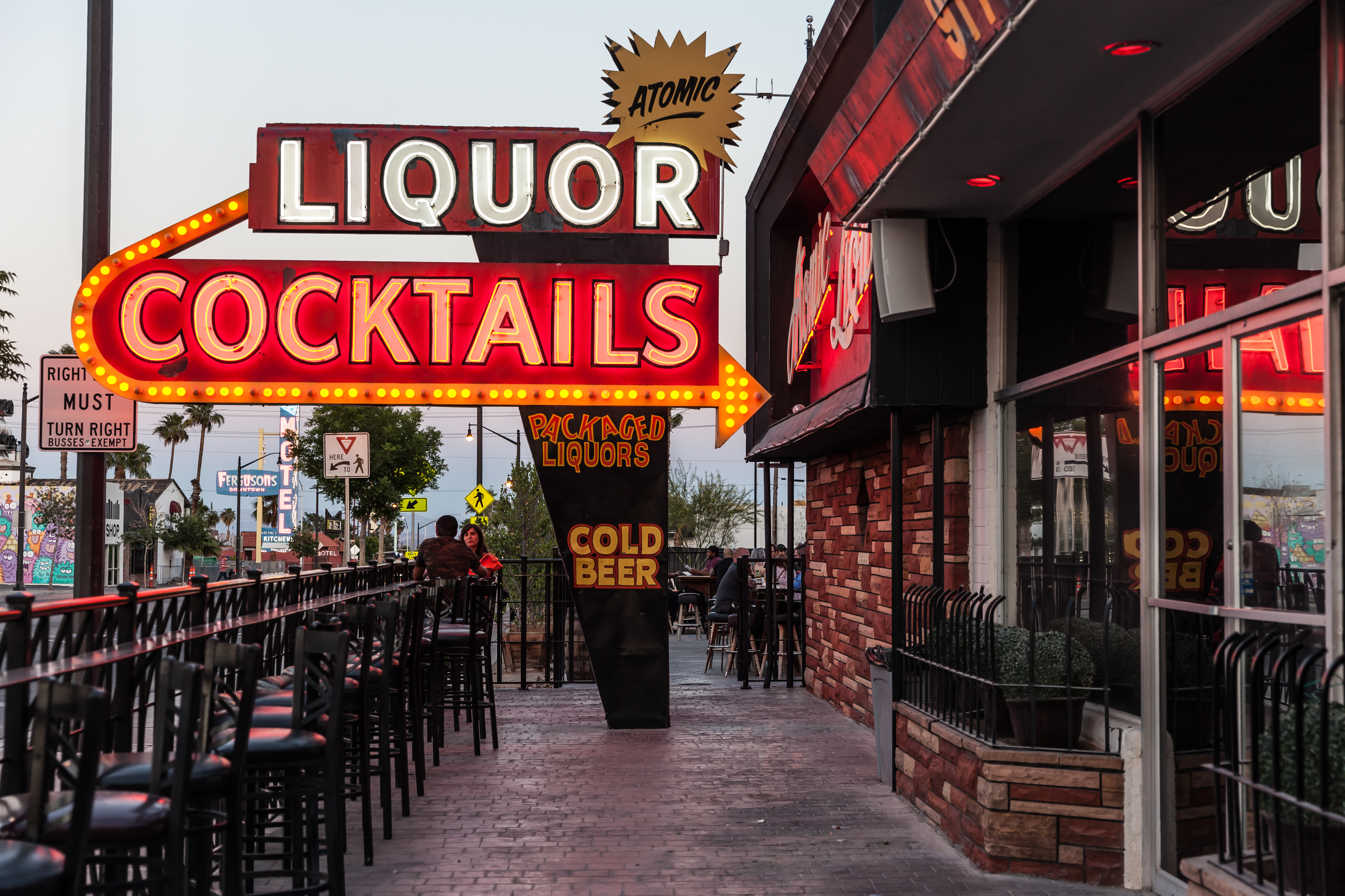 An outdoor patio with a neon sign that says Liquor, Cocktails