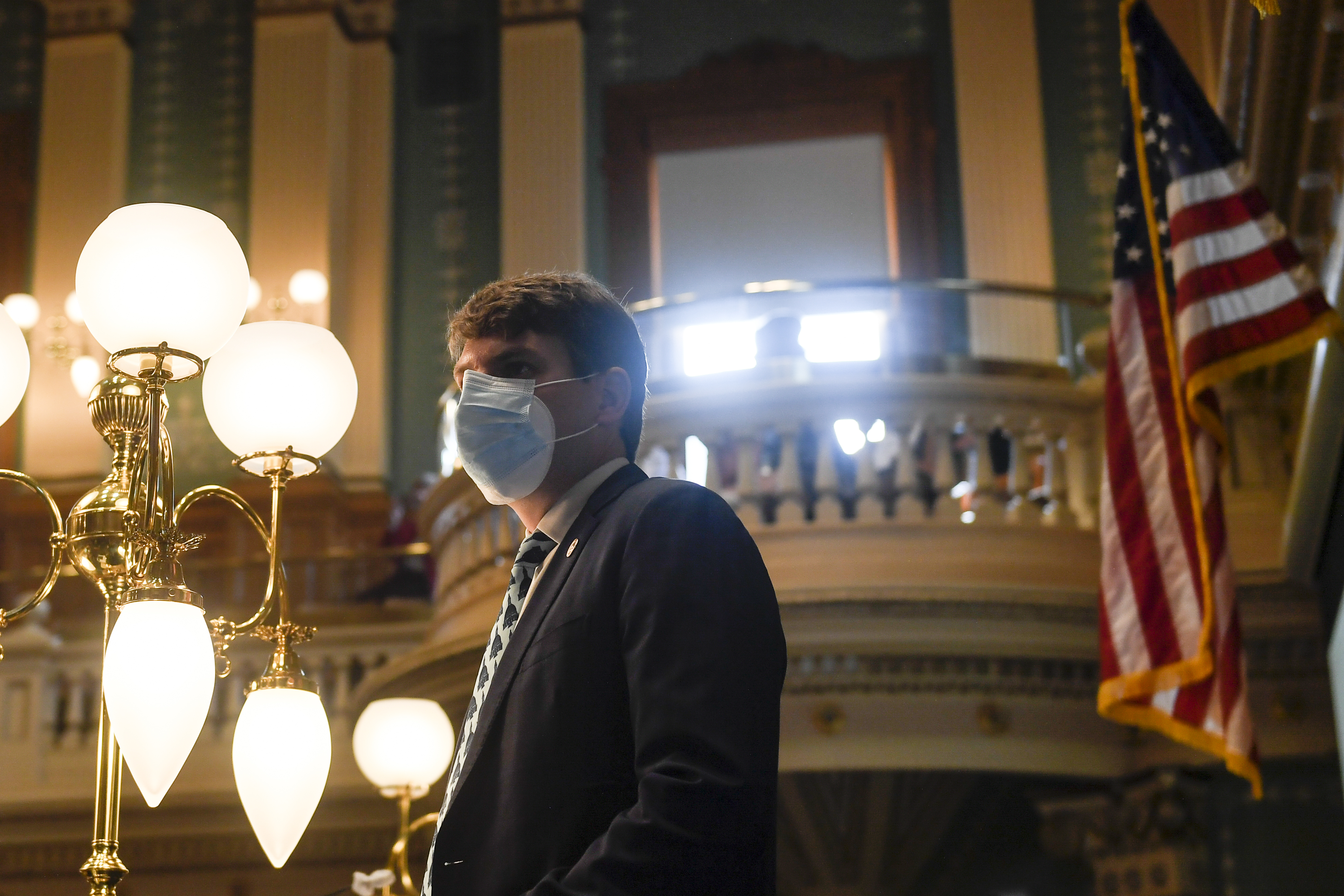 Colorado Speaker of the House Alec Garnett listens to an introduction in the State House chambers. He is wearing mask in an ornate room.