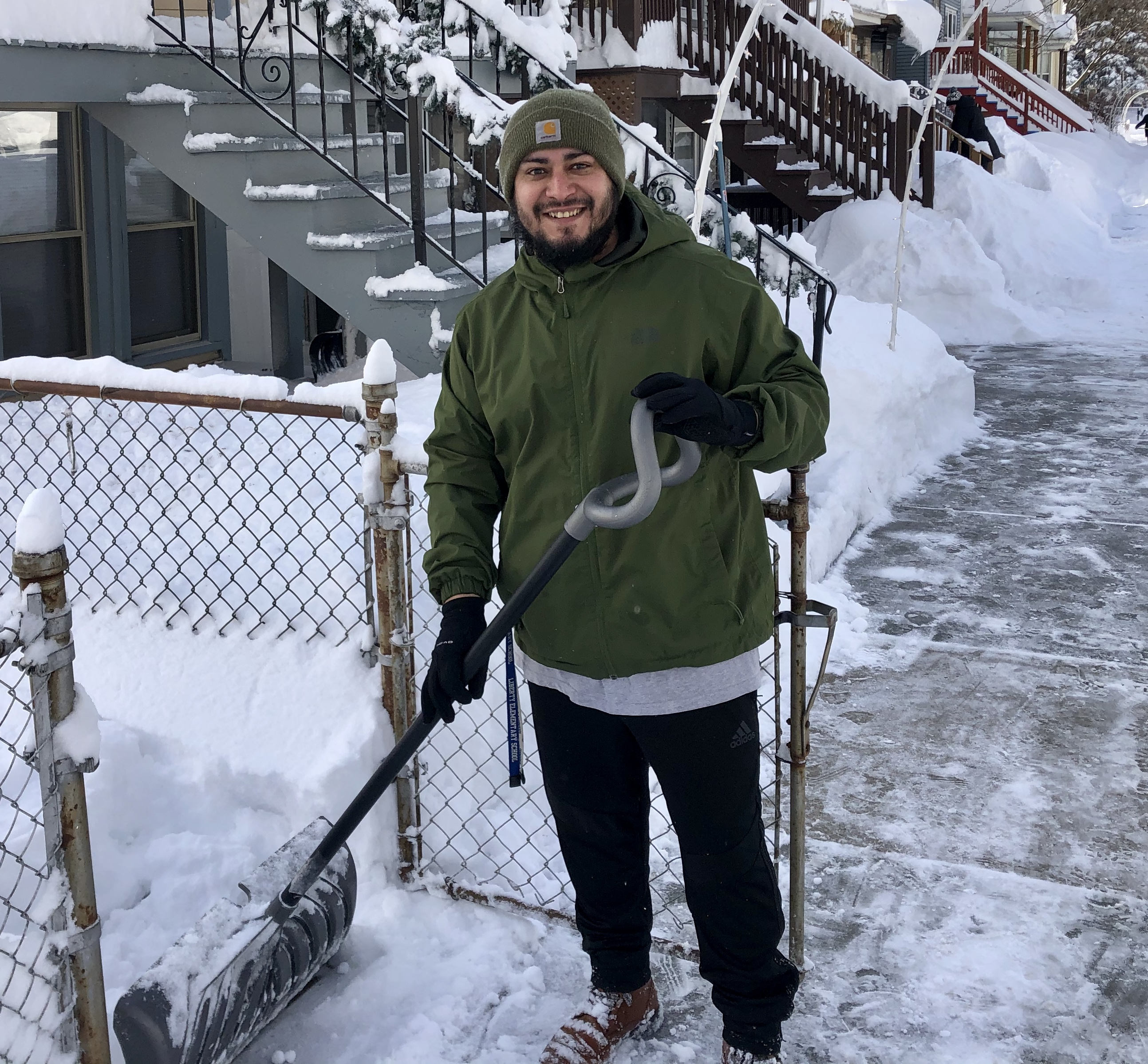 Fernando Melquiades shovels snow Tuesday at his home in Irving Park.