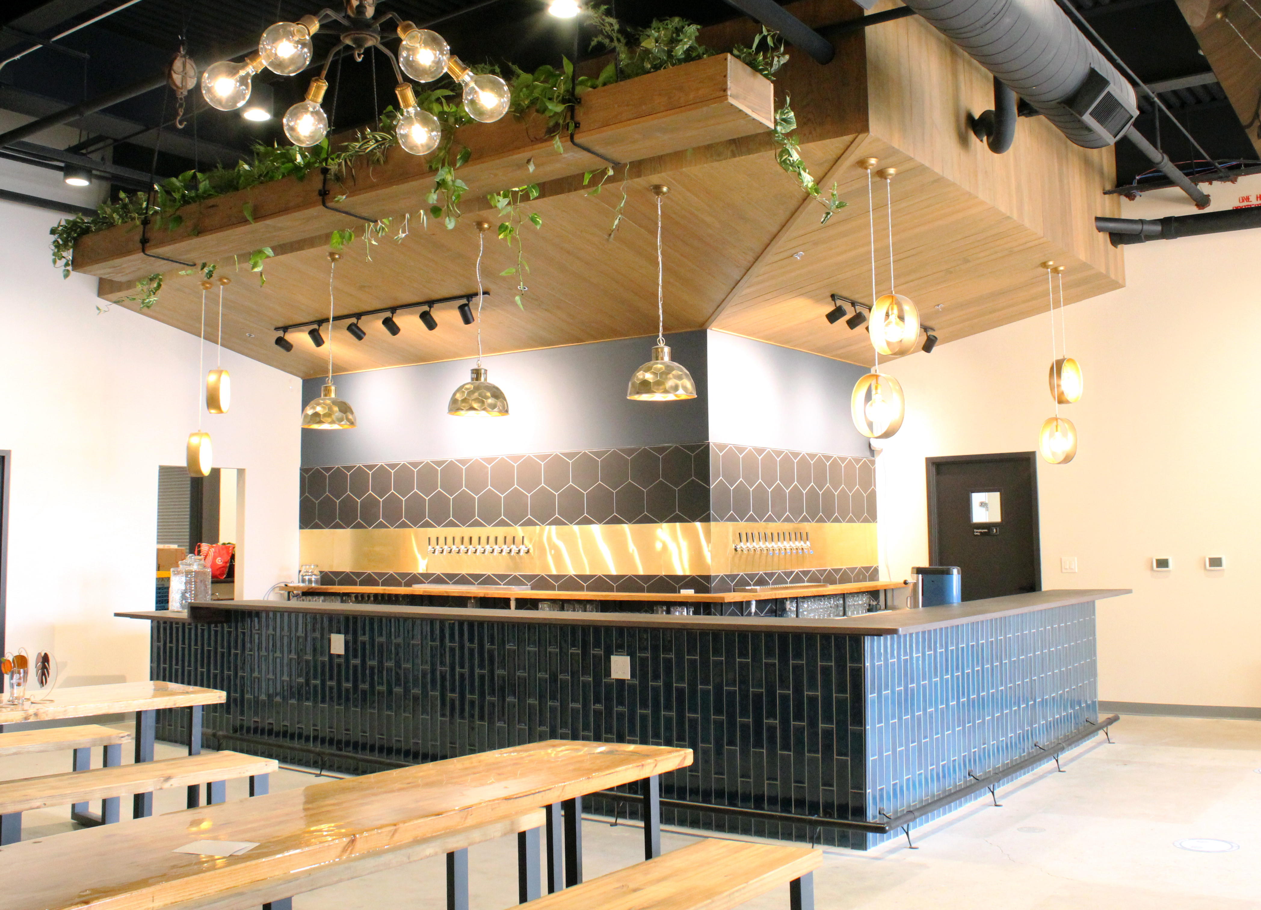 The gray tiled u-shaped bar with six hanging gold pendant lights and two blonde wood picnic tables with benches in the taproom at Roundtrip Brewing in Atlanta