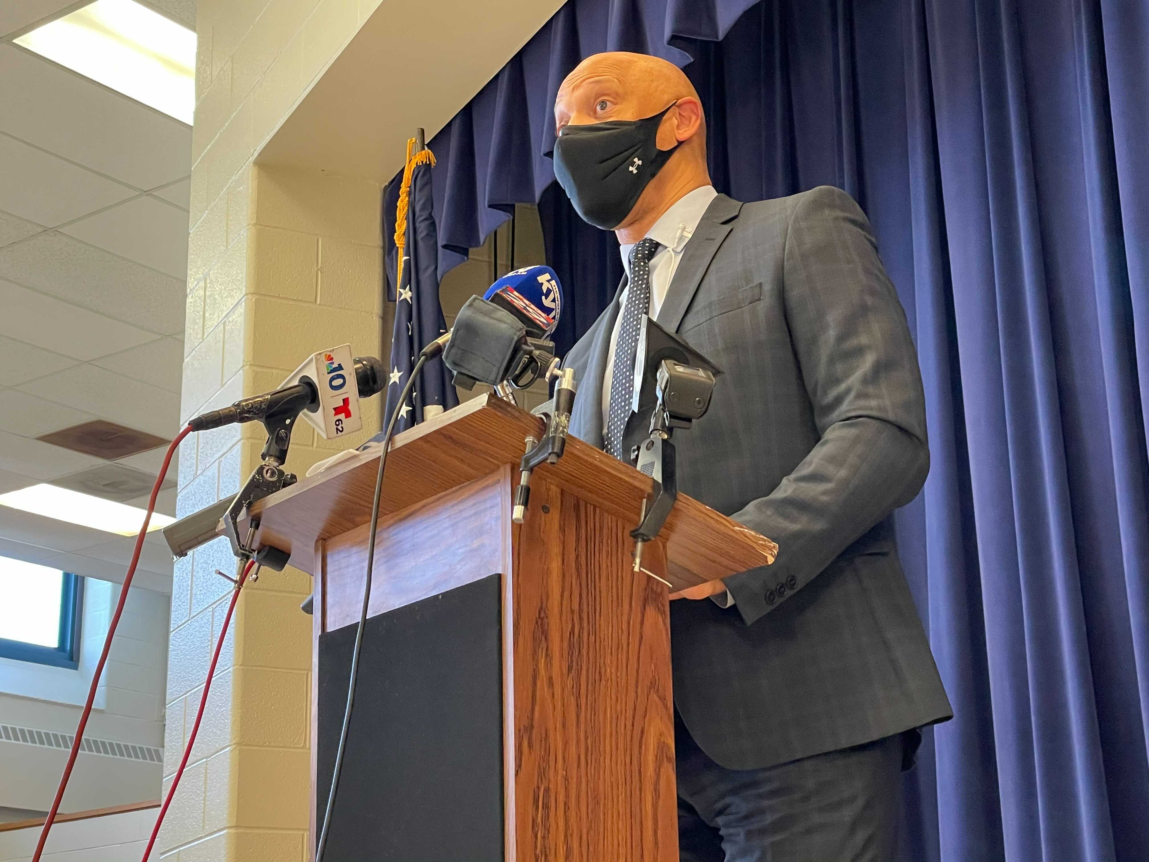 William Hite wearing a face mask standing at a podium with microphones.