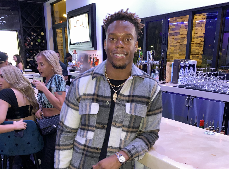 A man stands at a bar in a plaid shirt
