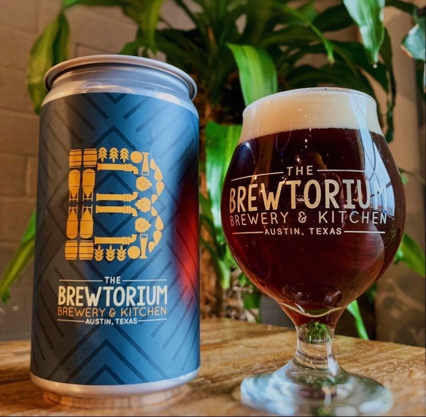 A can of beer and a tulip glass full of beer from Brewtorium sits on a wooden table.