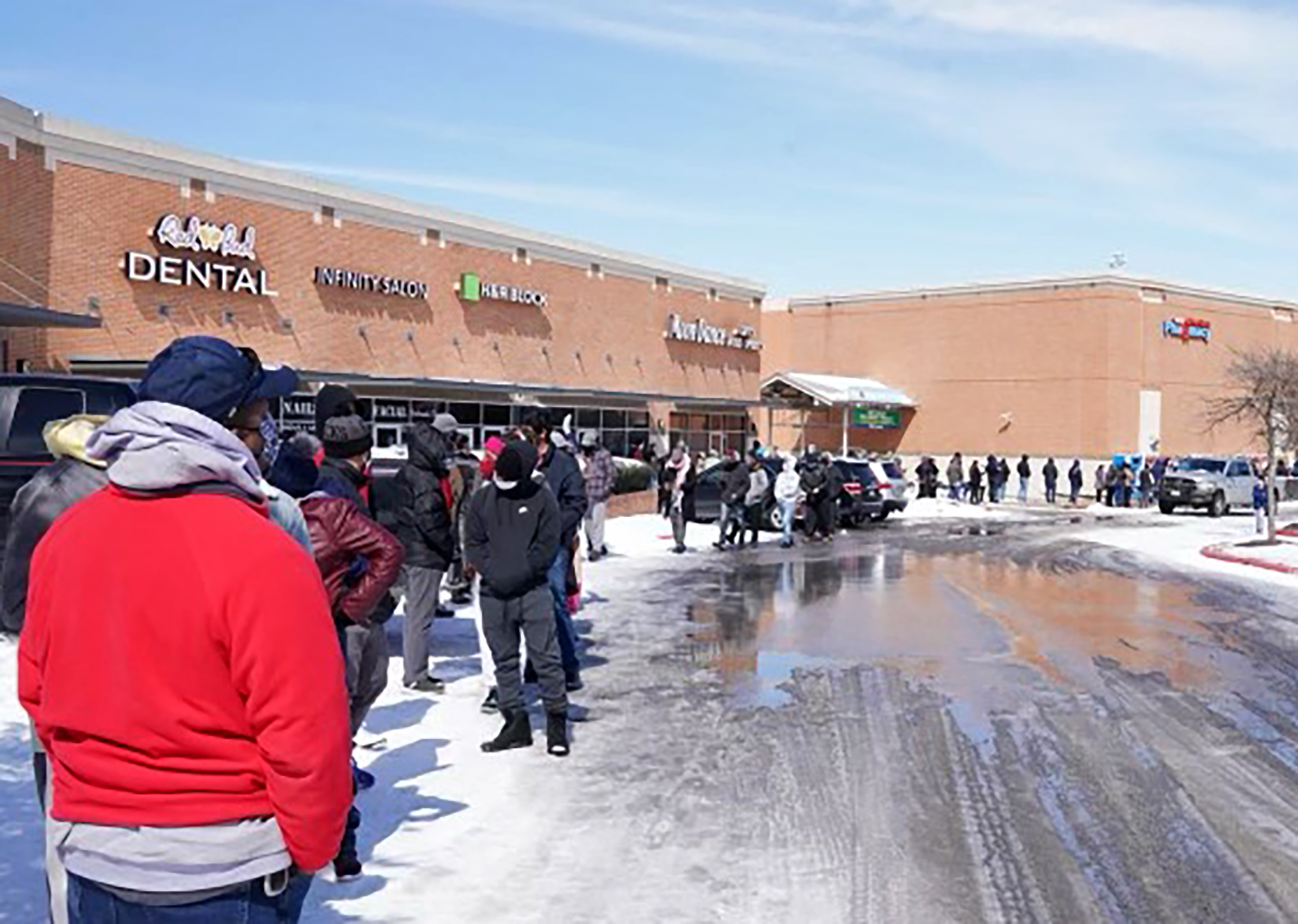 Long line of people outside in a shopping plaza.