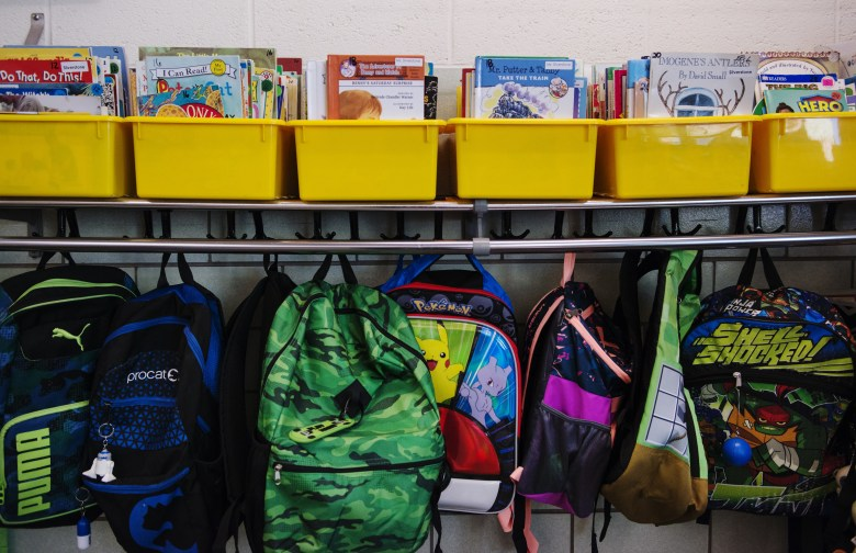 Books in yellow bins sit on a shelf and backpacks hang from hooks in a classroom.
