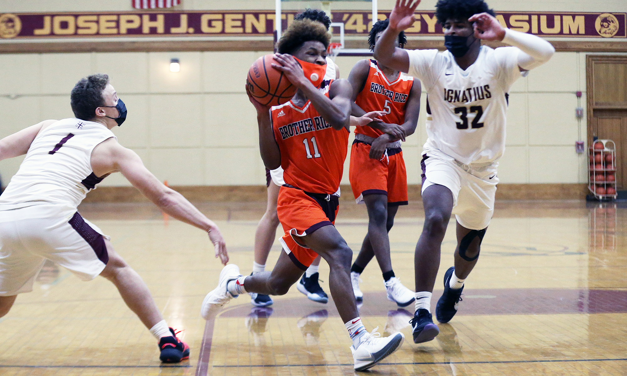Brother Rice's Ahmad Henderson (11) finds a crease and slashes toward the basket as St. Ignatius' Parker Higginbottom (1) and Kolby Gilles (32) defend.