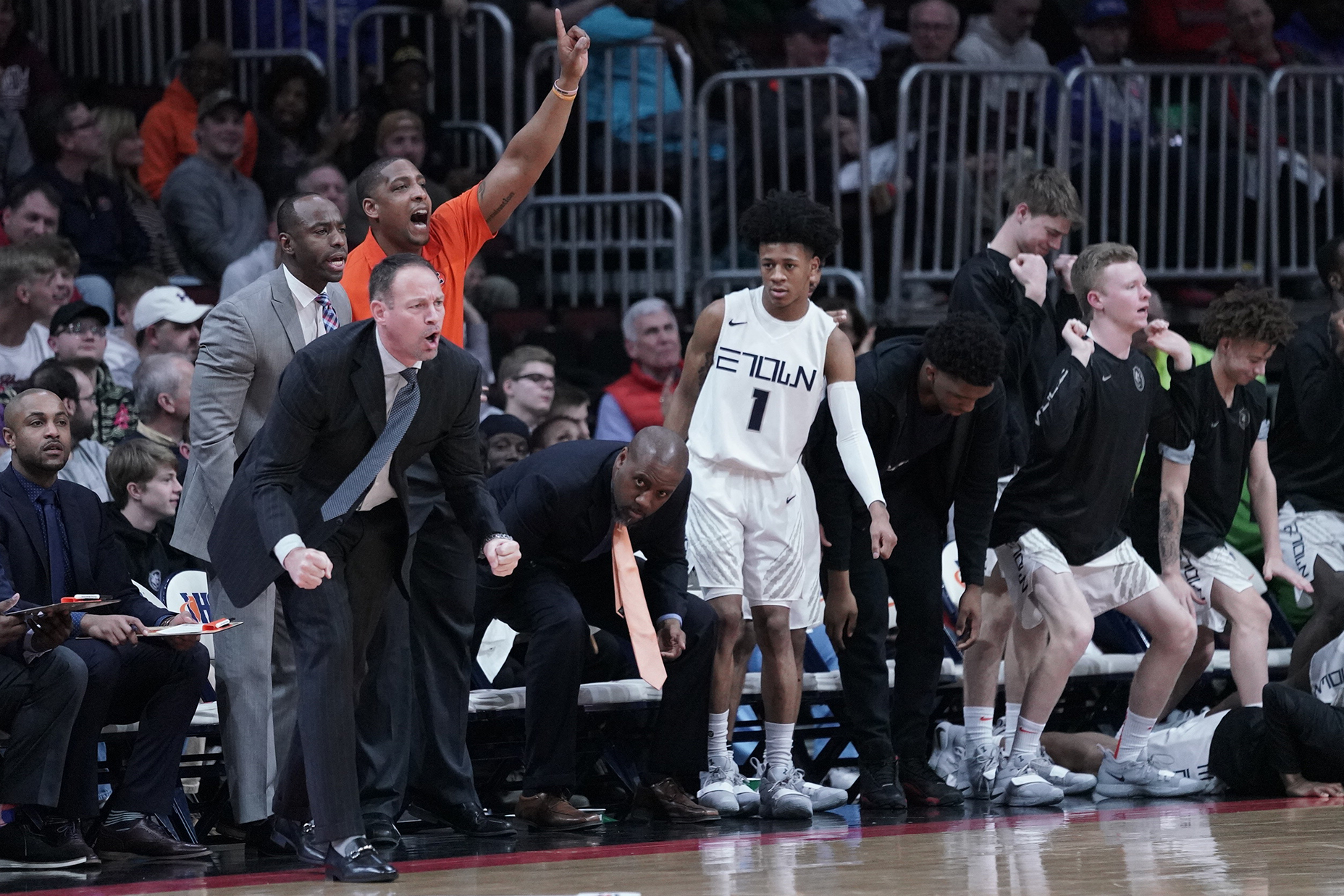 Evanston coach Mike Ellis and his team jumps up after a call an official made against Rockford East.