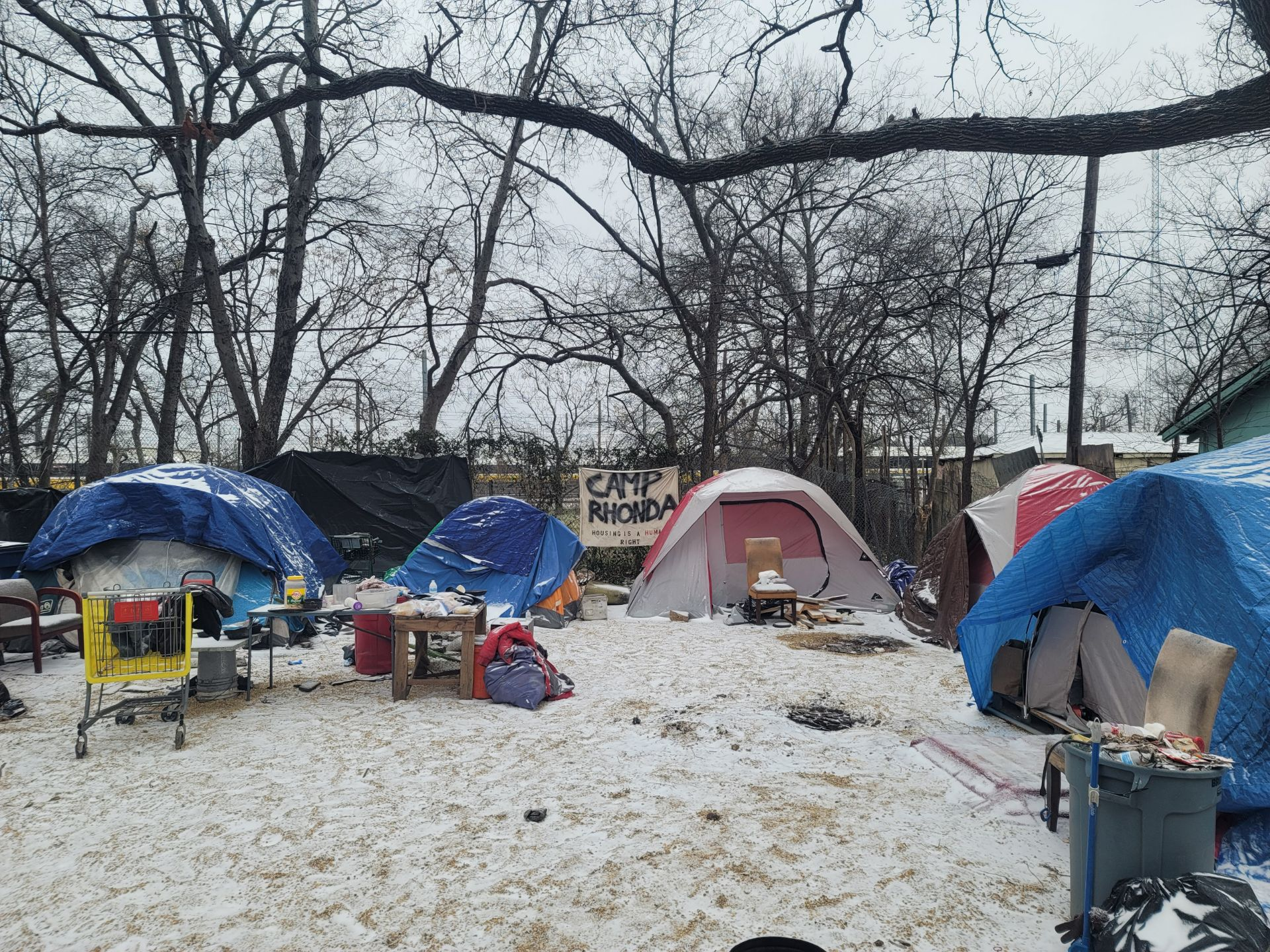 A photo of Dallas homeless encampment Camp Rhonda. Snow-covered tents are set up on a snow-covered ground.