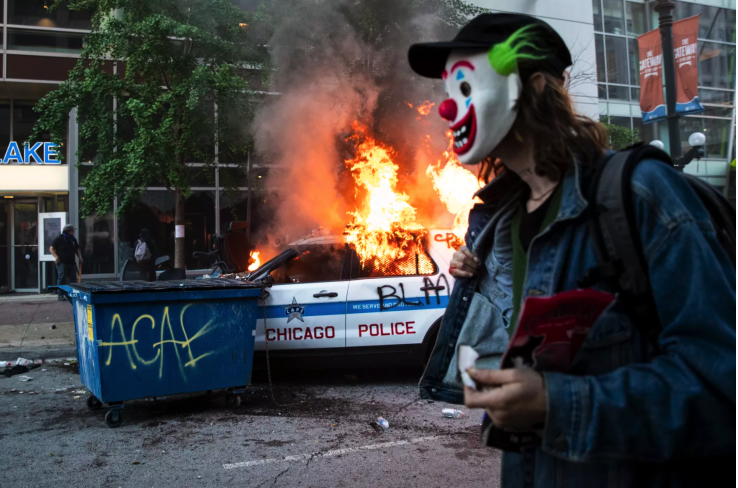 A man in a Joker mask stands near a burning Chicago police squad on May 30 in the 200 block of North State. The man was later identified as Timothy O'Donnell in a federal complaint charging him with arson.