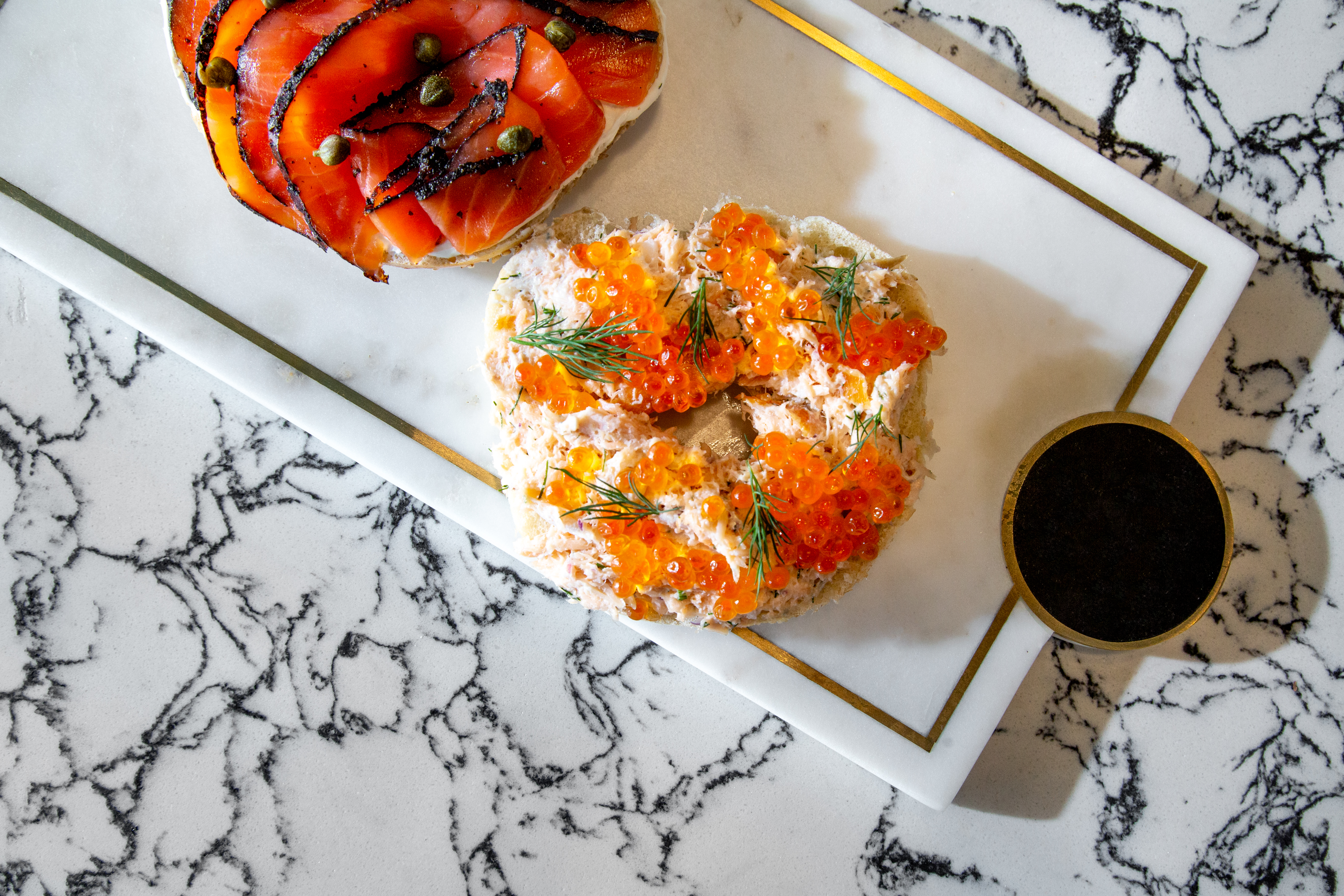 Two bagels, one with lox and one with smoked salmon and roe