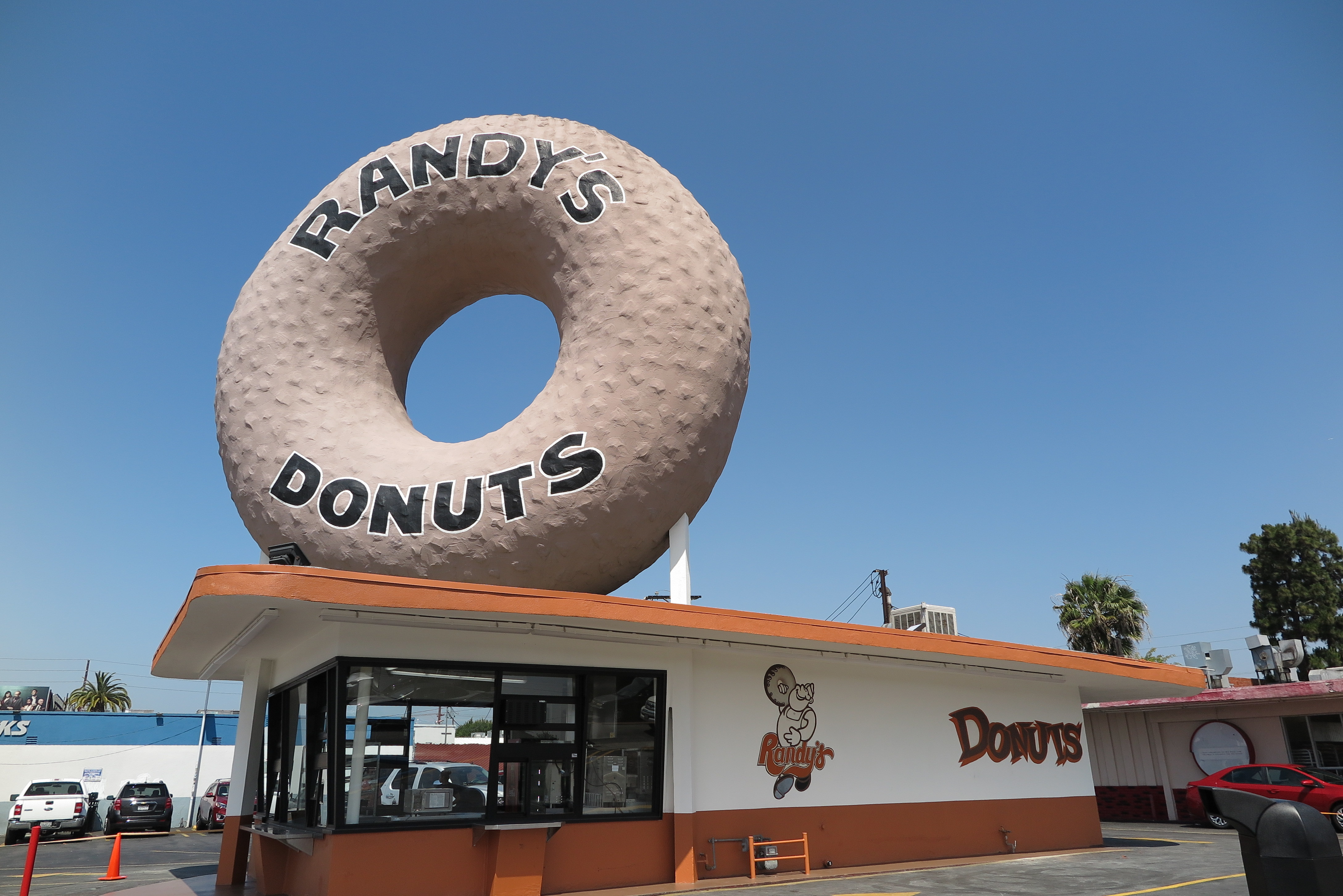 The exterior of a doughnut shop with a giant doughnut on top of it