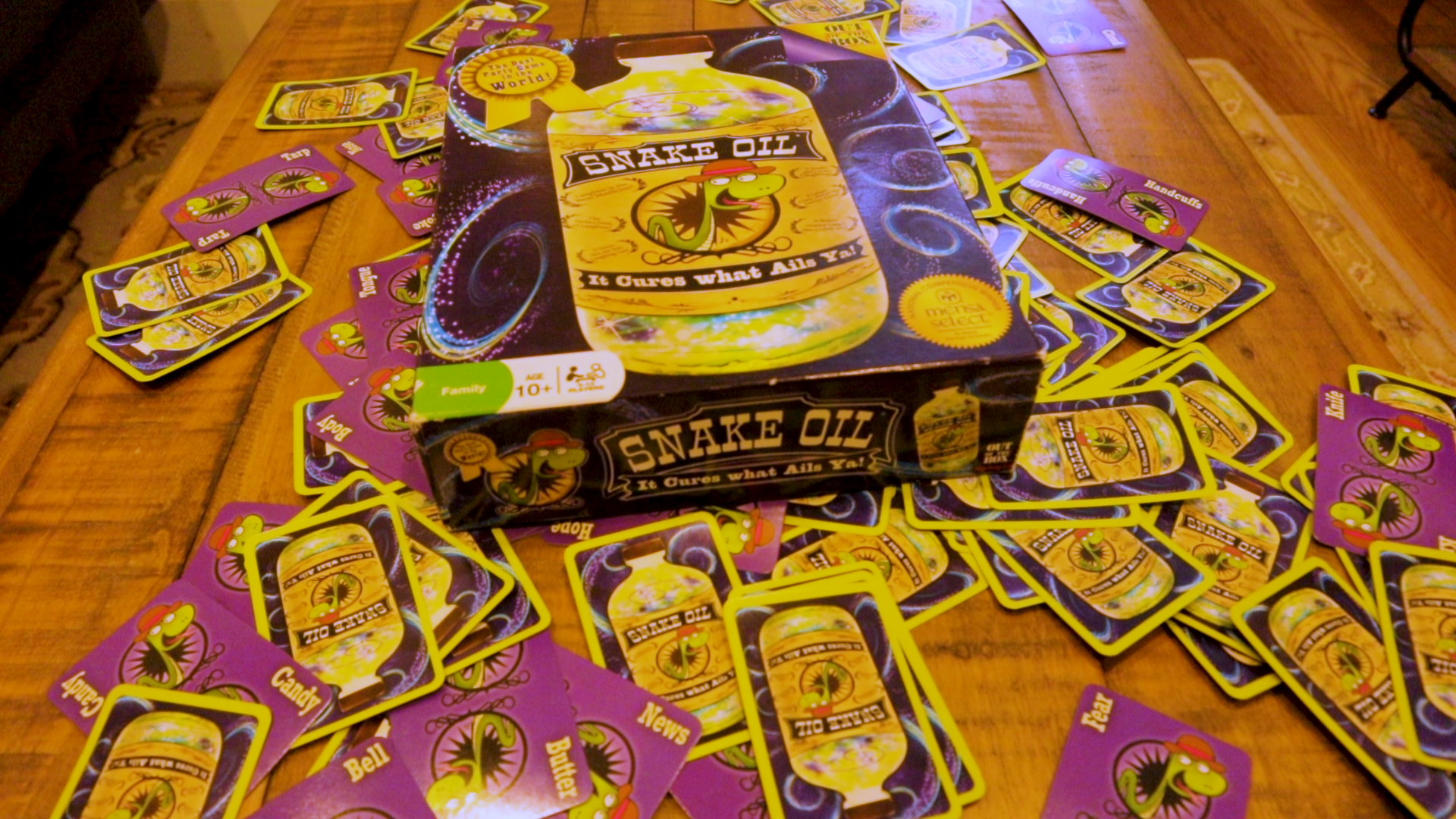 The box to the board game Snake Oil sits on a pile of cards from the game.