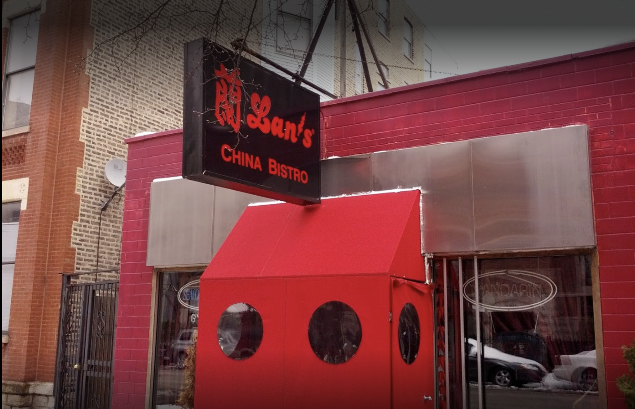 Snows on the ground outside a restaurant storefront with a sign and a red vestibule.