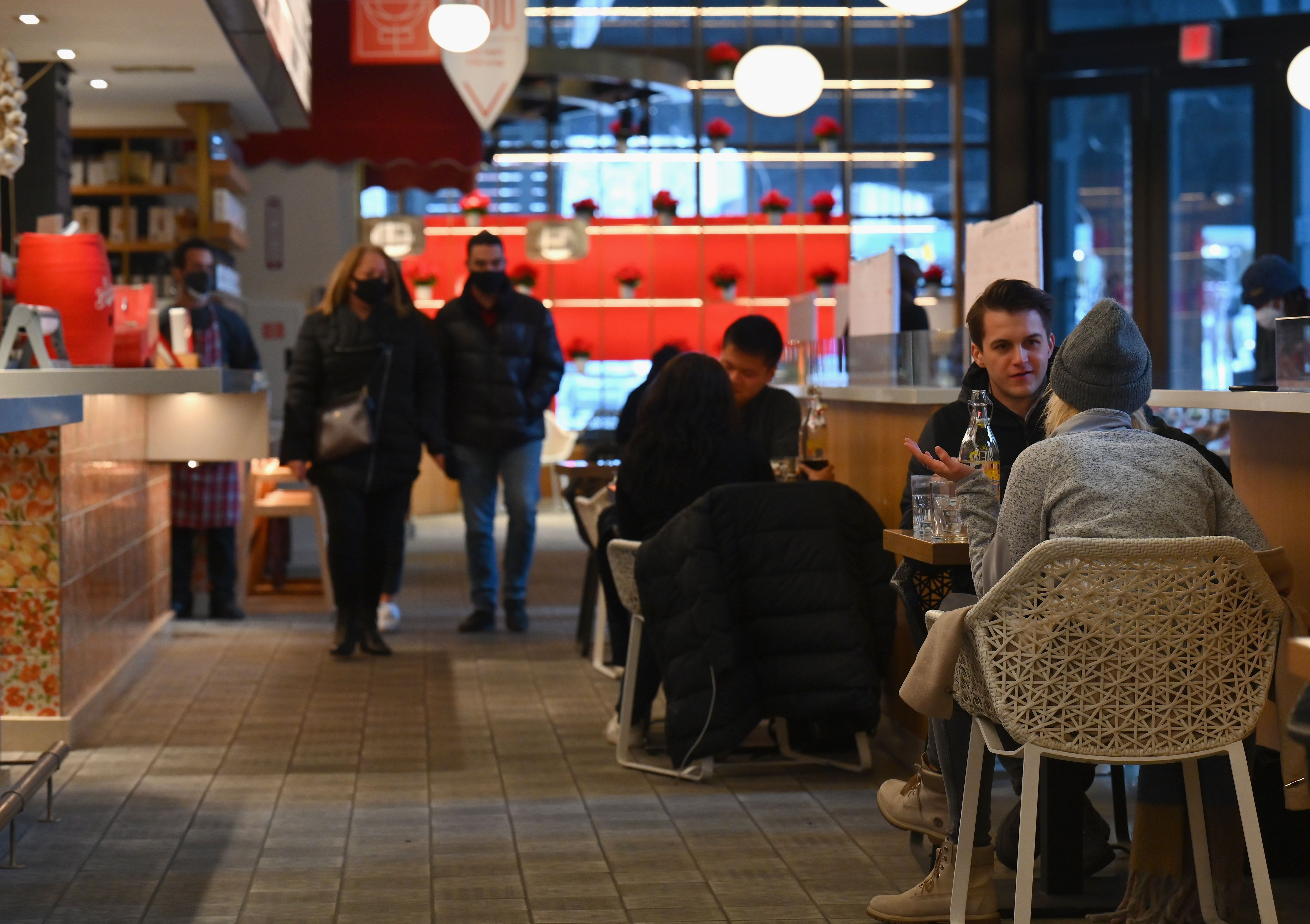 Diners sitting and eating inside a Hudson Yards restaurant indoors