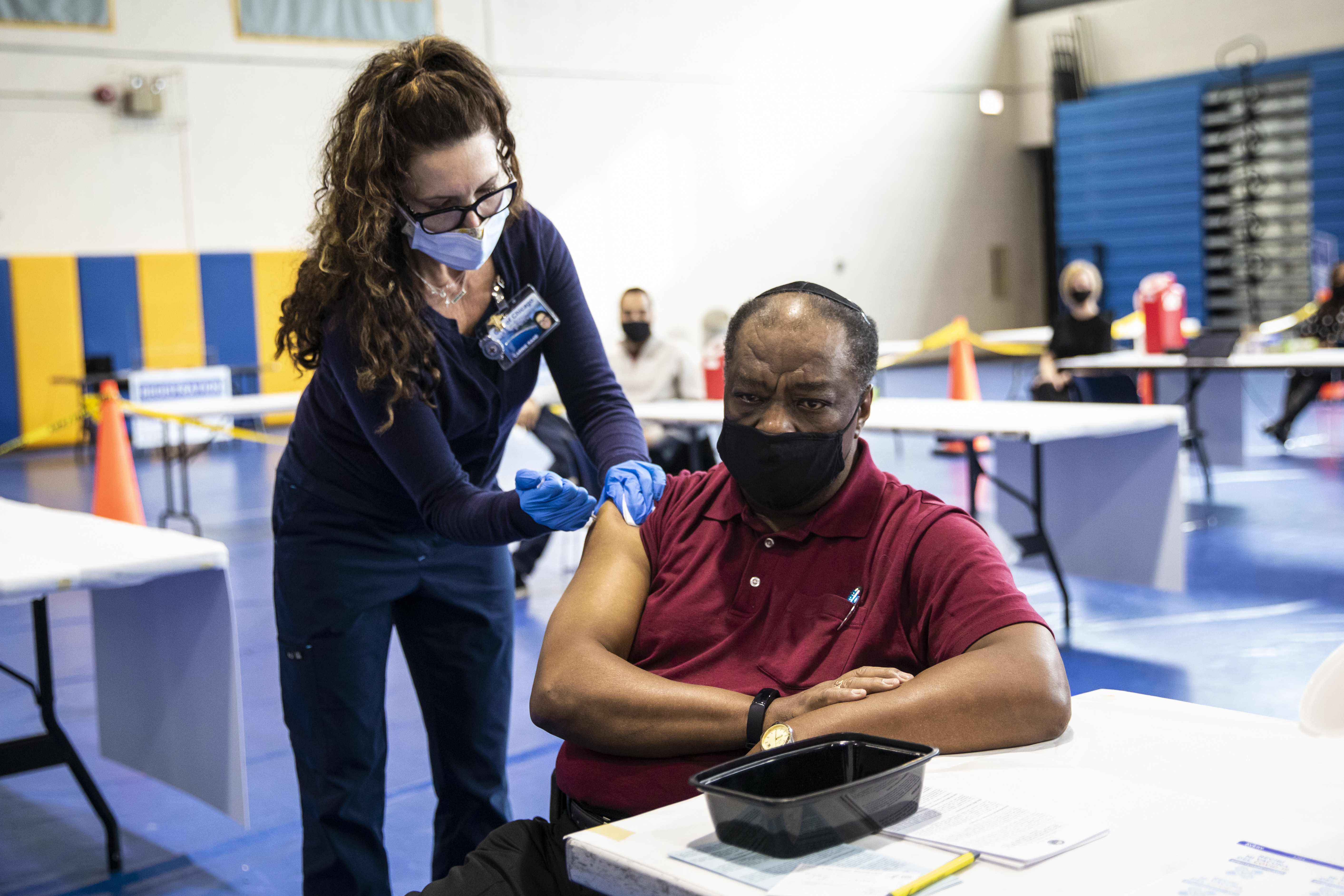 A Pfizer-BioNTech COVID-19 vaccine dose is administered at Richard J. Daley College last month.