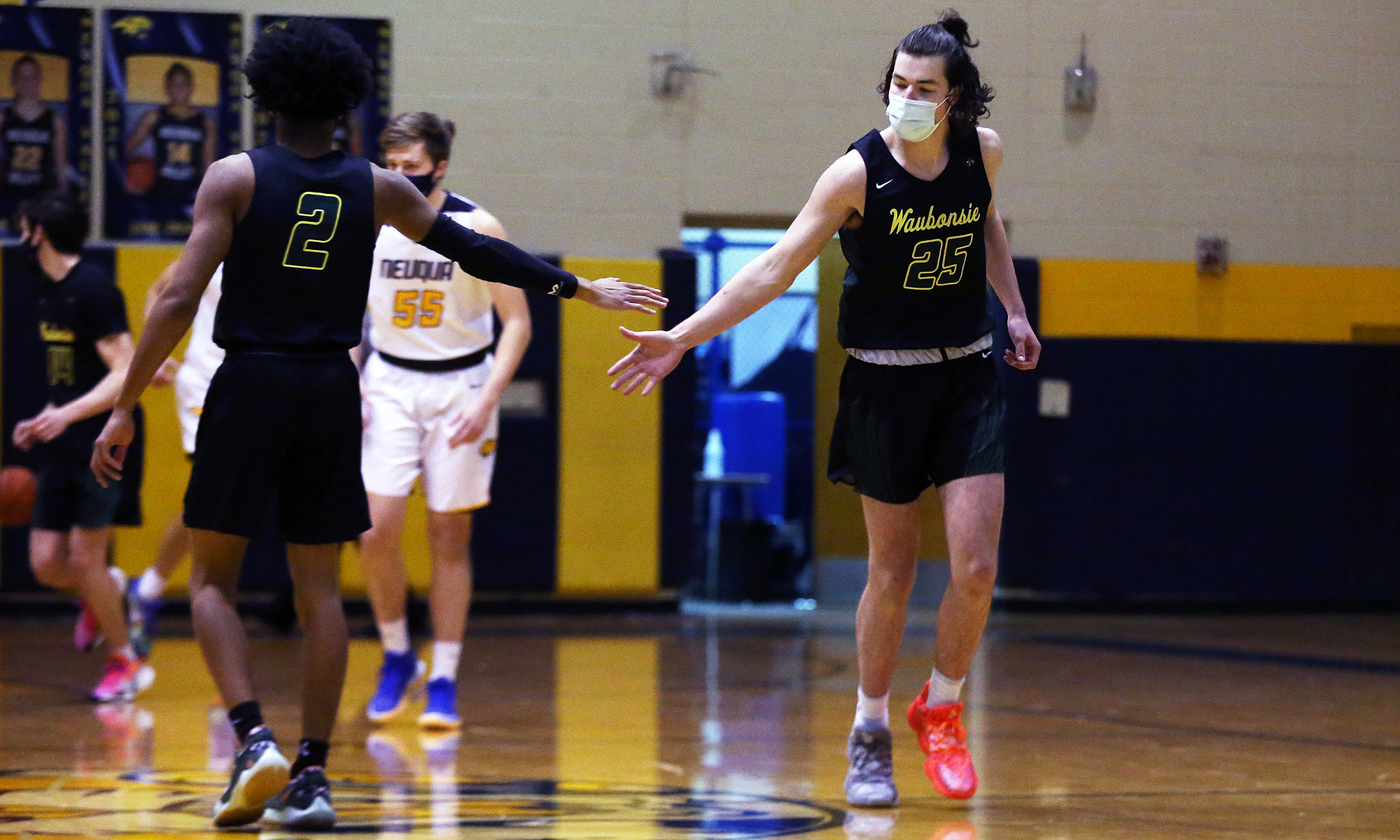 Waubonsie Valley's Isaiah Smith (2) congratulates Carter Langendorf (25) after a good play.