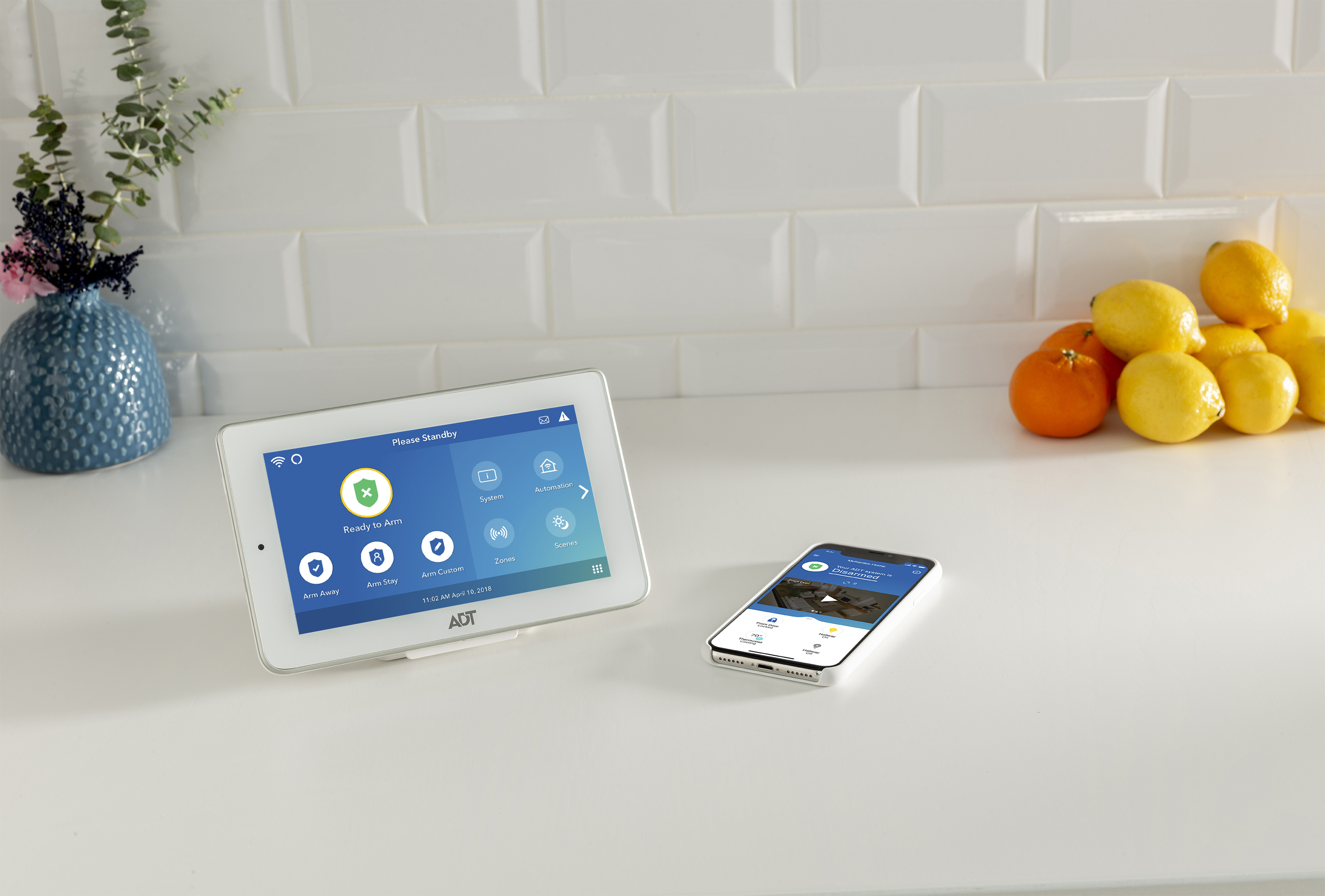 A tablet and phone sit on a kitchen counter, and both devices have the ADT Security app on display.