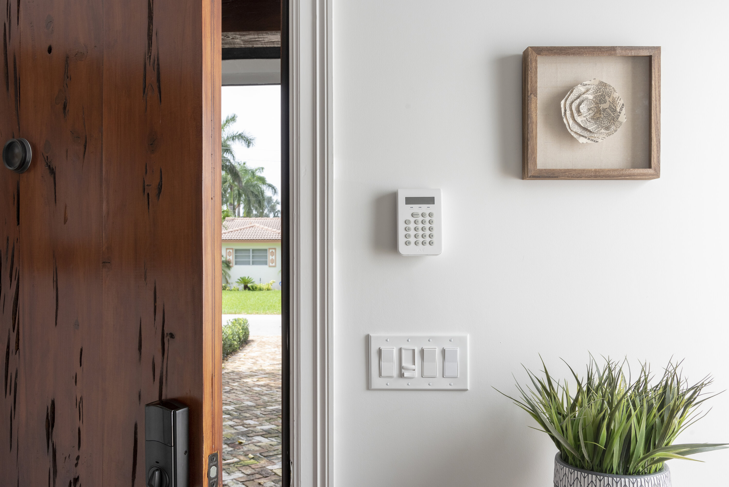 A door is slightly open, and to the right of it is a touchpad security system on the wall.