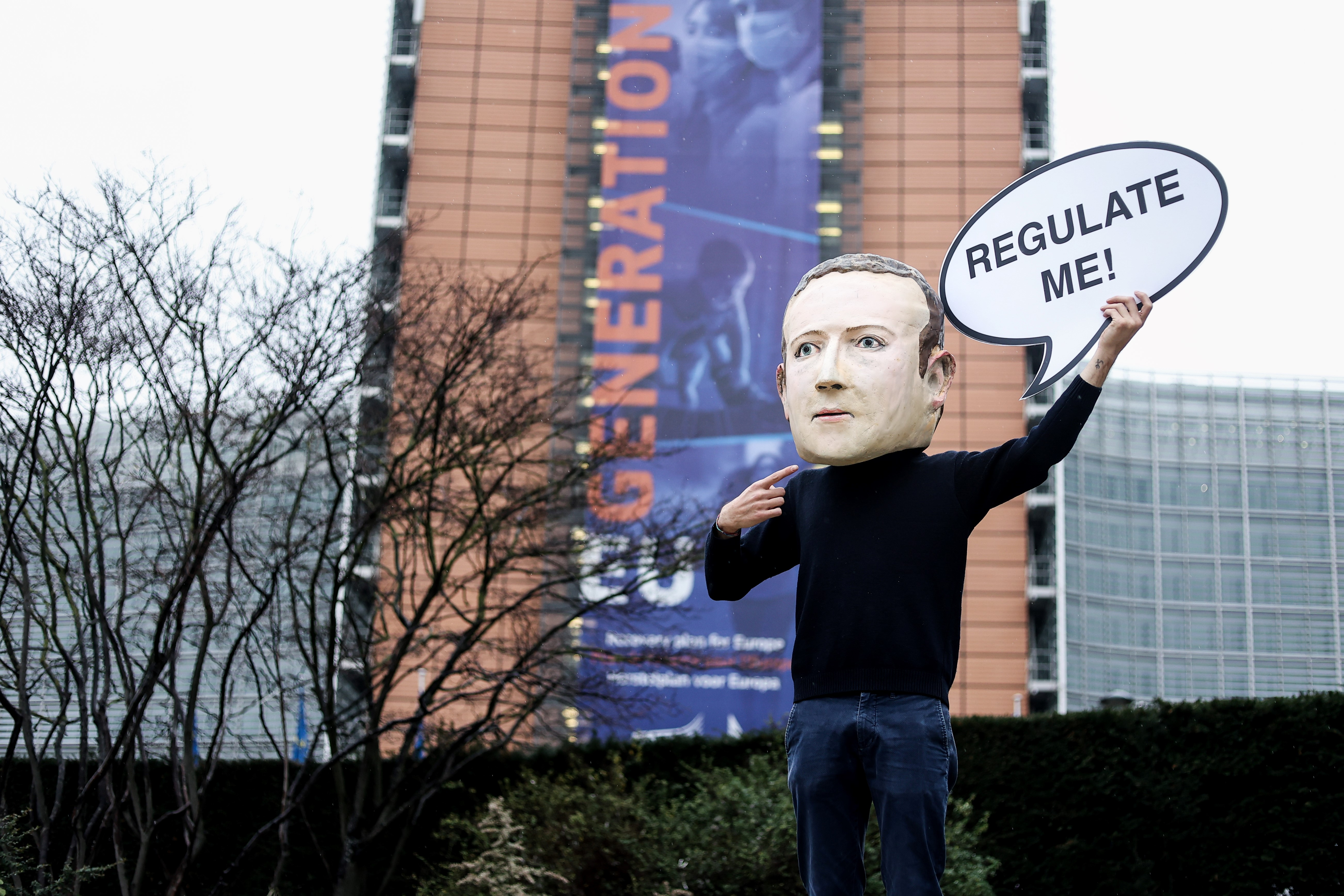 """An activist of environmental NGO Avaaz wearing a mask depicting Facebook CEO Mark Zuckerberg holds a banner reading """"Regulate me"""" during an action marking the release of the Digital Services Act, outside the European Commission building in Brussels on December 15, 2020."""