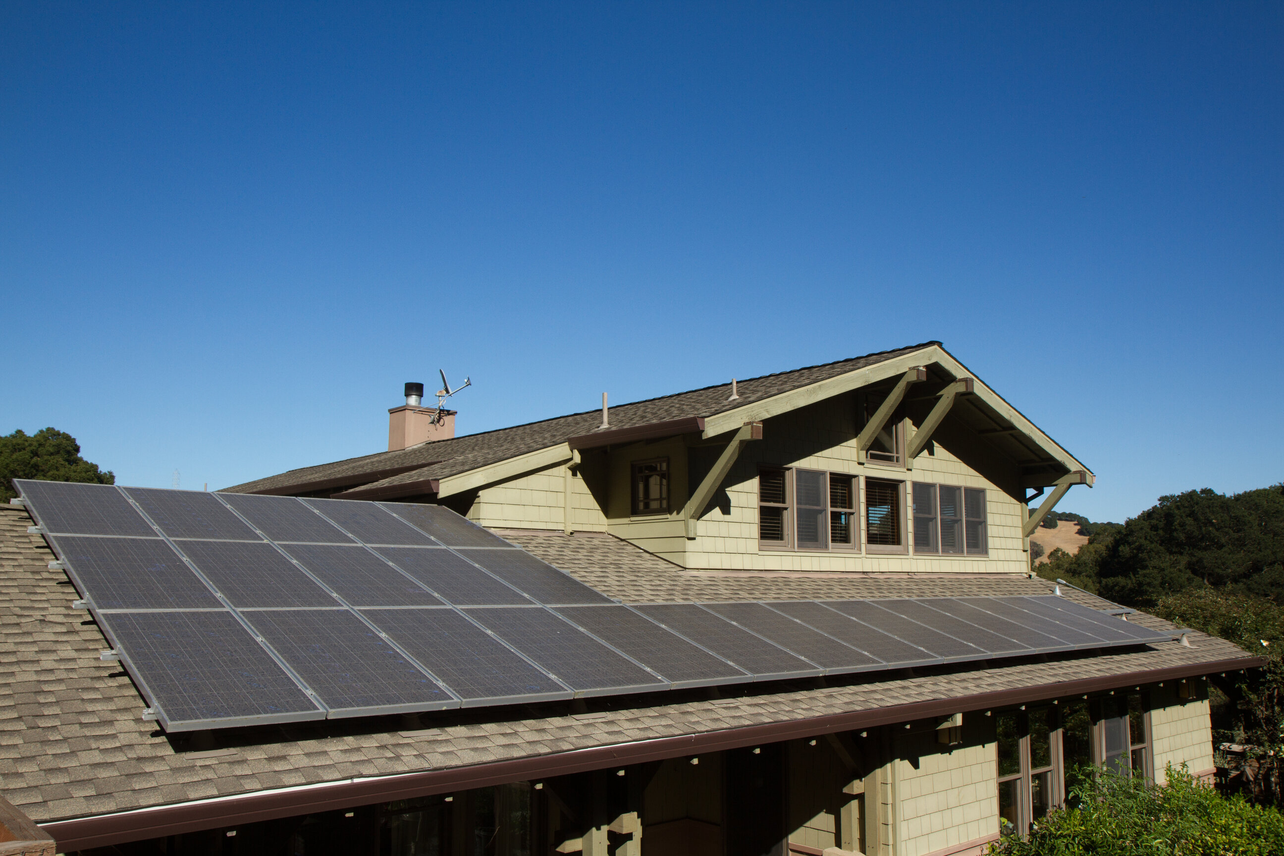 A green home with solar panels on the roof.