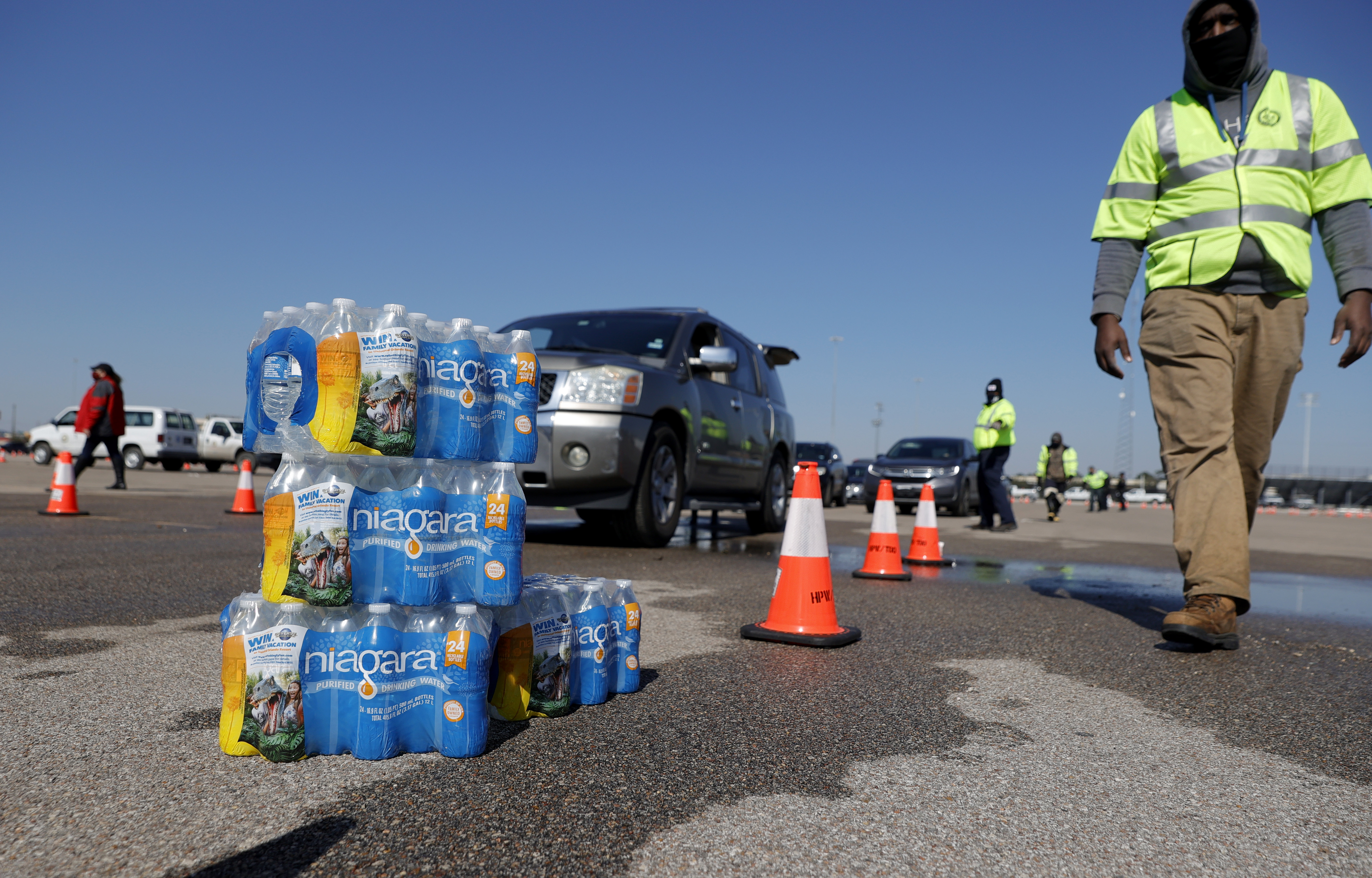 A Black man in a reflective neon vest walks toward piled cases of water, as cars line up behind him.