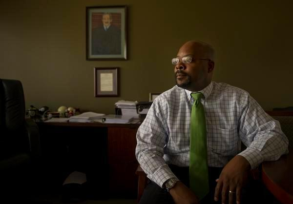 Aurora Superintendent Rico Munn, wearing a green tie and glasses, poses for a portrait while seated. A portrait of Supreme Court Justice Thurgood Marshall hangs on the wall.