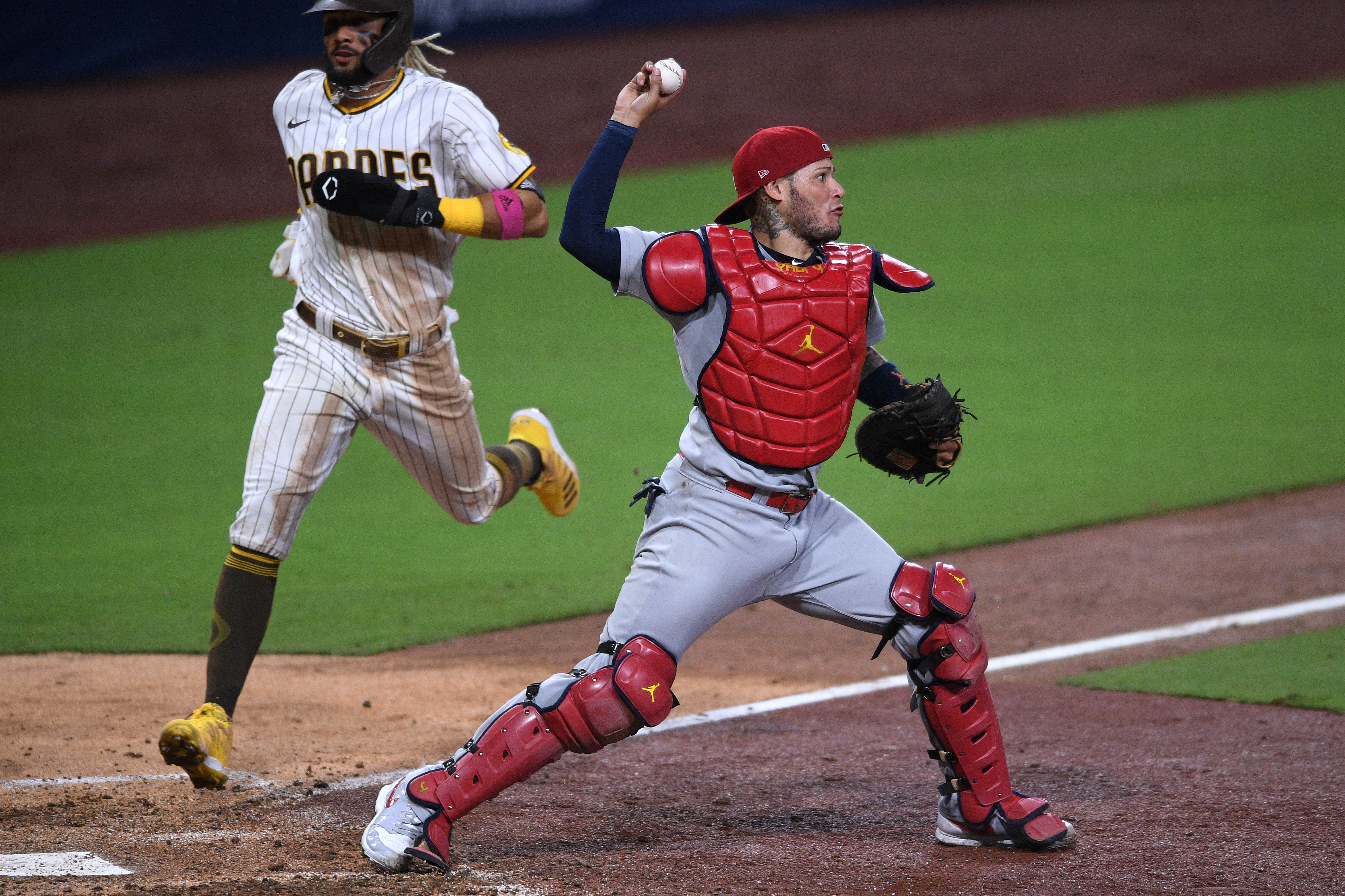 St. Louis Cardinals catcher Yadier Molina (right) throws to second base after forcing out San Diego Padres shortstop Fernando Tatis Jr. (left) at home during the seventh inning at Petco Park.