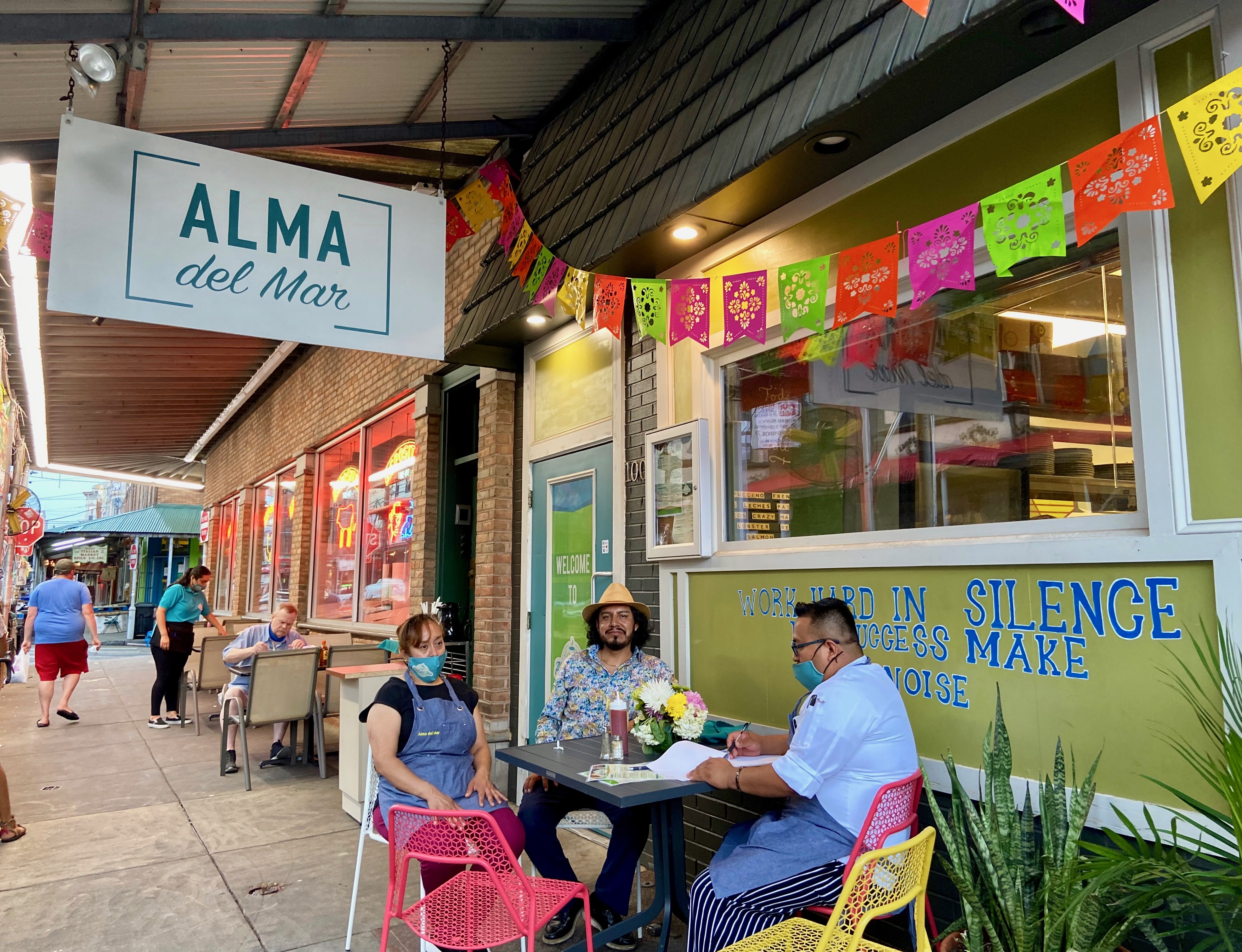 three people at table outside restaurant with sign that says alma del mar