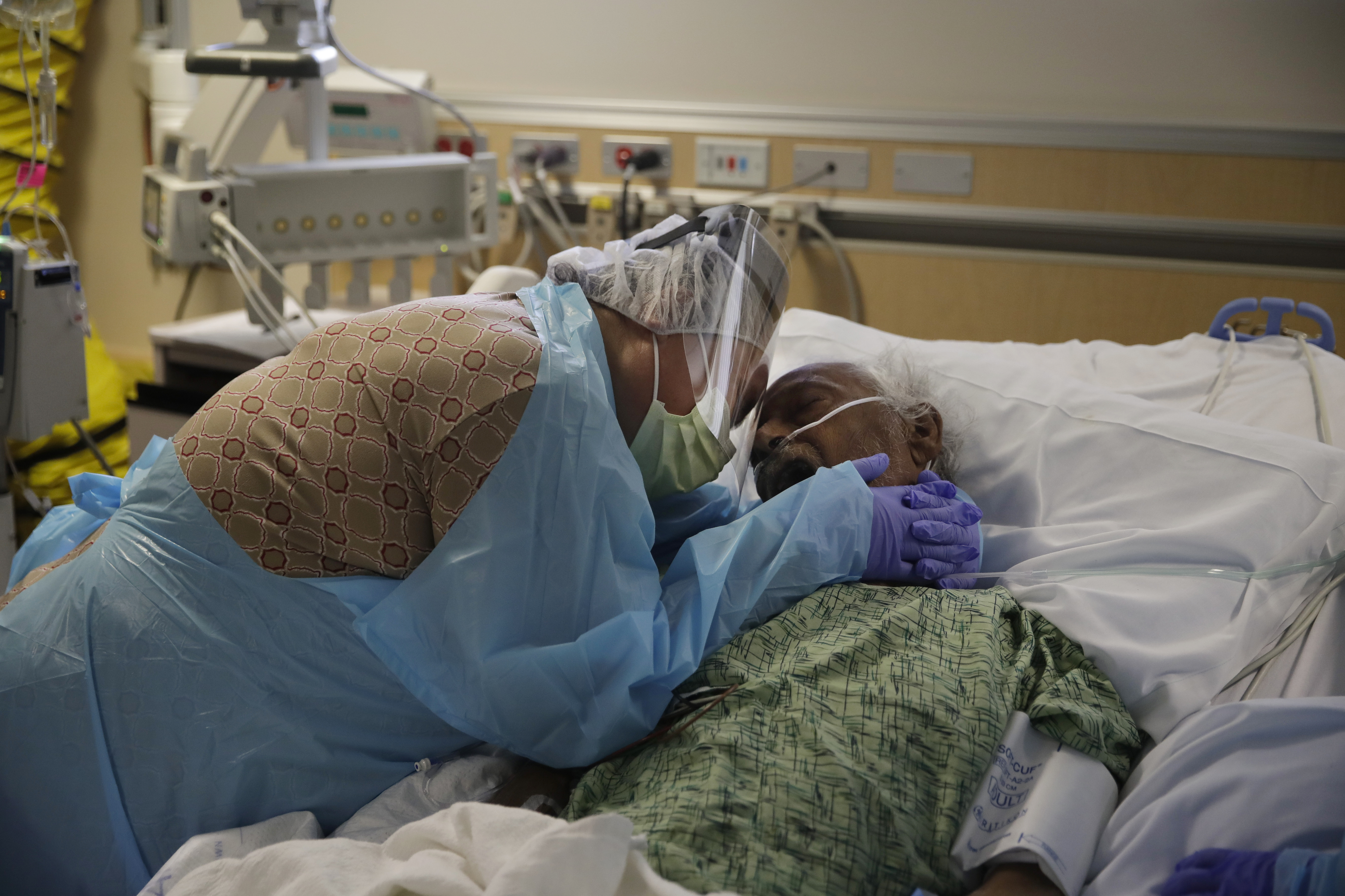 In this July 31, 2020, file photo, Romelia Navarro, 64, weeps while hugging her husband, Antonio, in his final moments in a COVID-19 unit at St. Jude Medical Center in Fullerton, Calif.