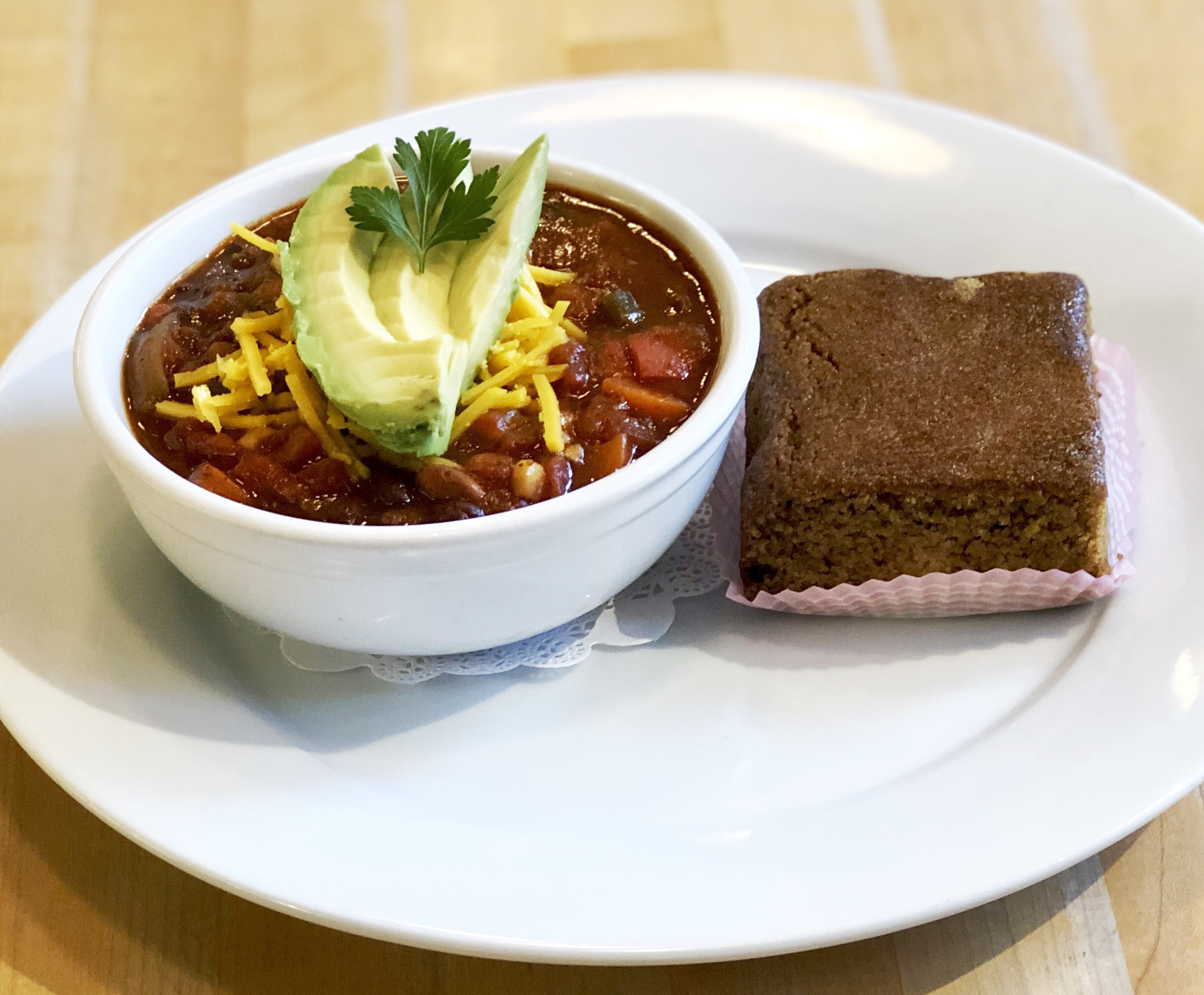 A white bowl of chili topped with slices of avocado sits next to a brown, brownie-like square of cornbead