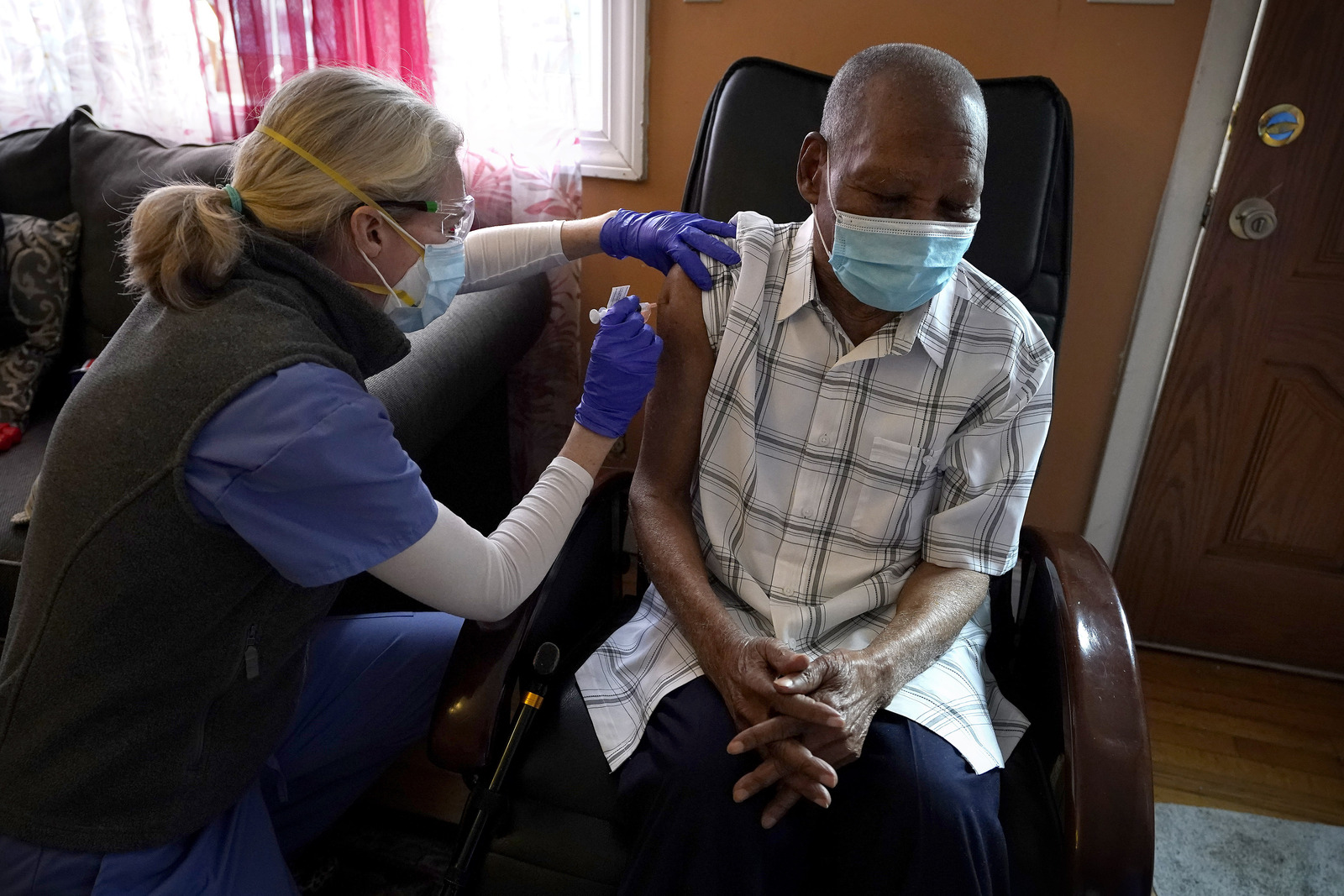 Geriatrician Dr. Megan Young gives Edouard Joseph, 91, a COVID-19 vaccination at his home in Boston's Mattapan neighborhood. Millions of U.S. residents will need COVID-19 vaccines brought to them because they rarely or never leave home.