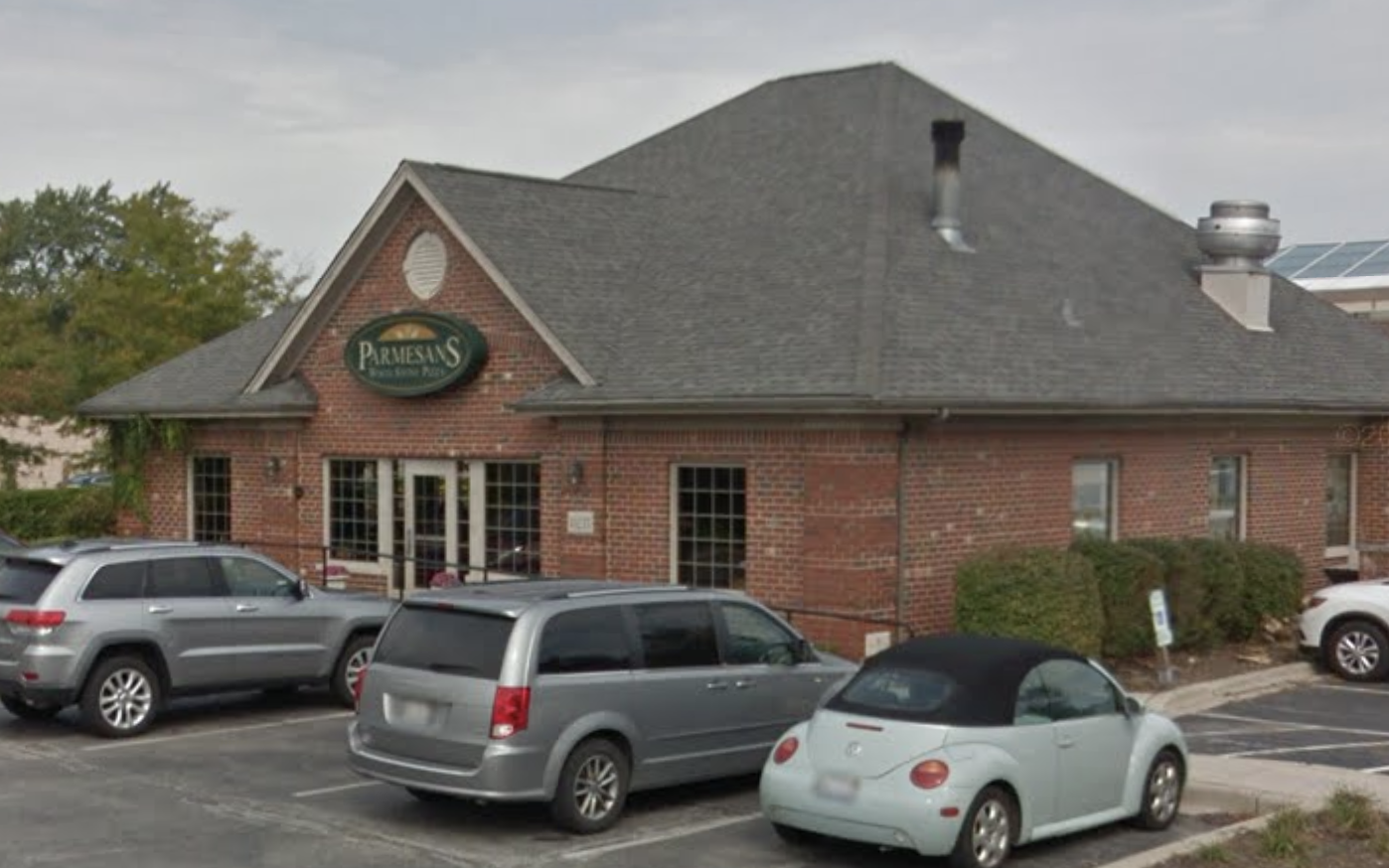 A large brick restaurant exterior with cars parked in front.