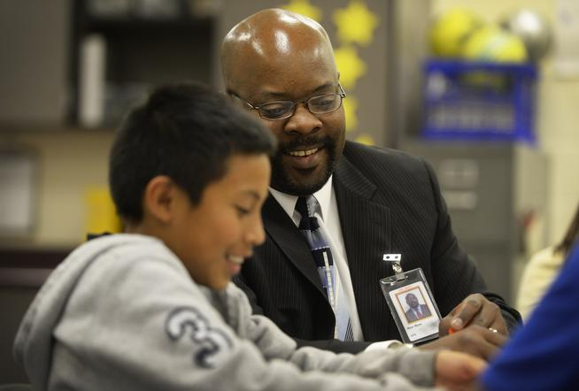 Aurora Public Schools Superintendent Rico Munn smiles with a student in a classroom.