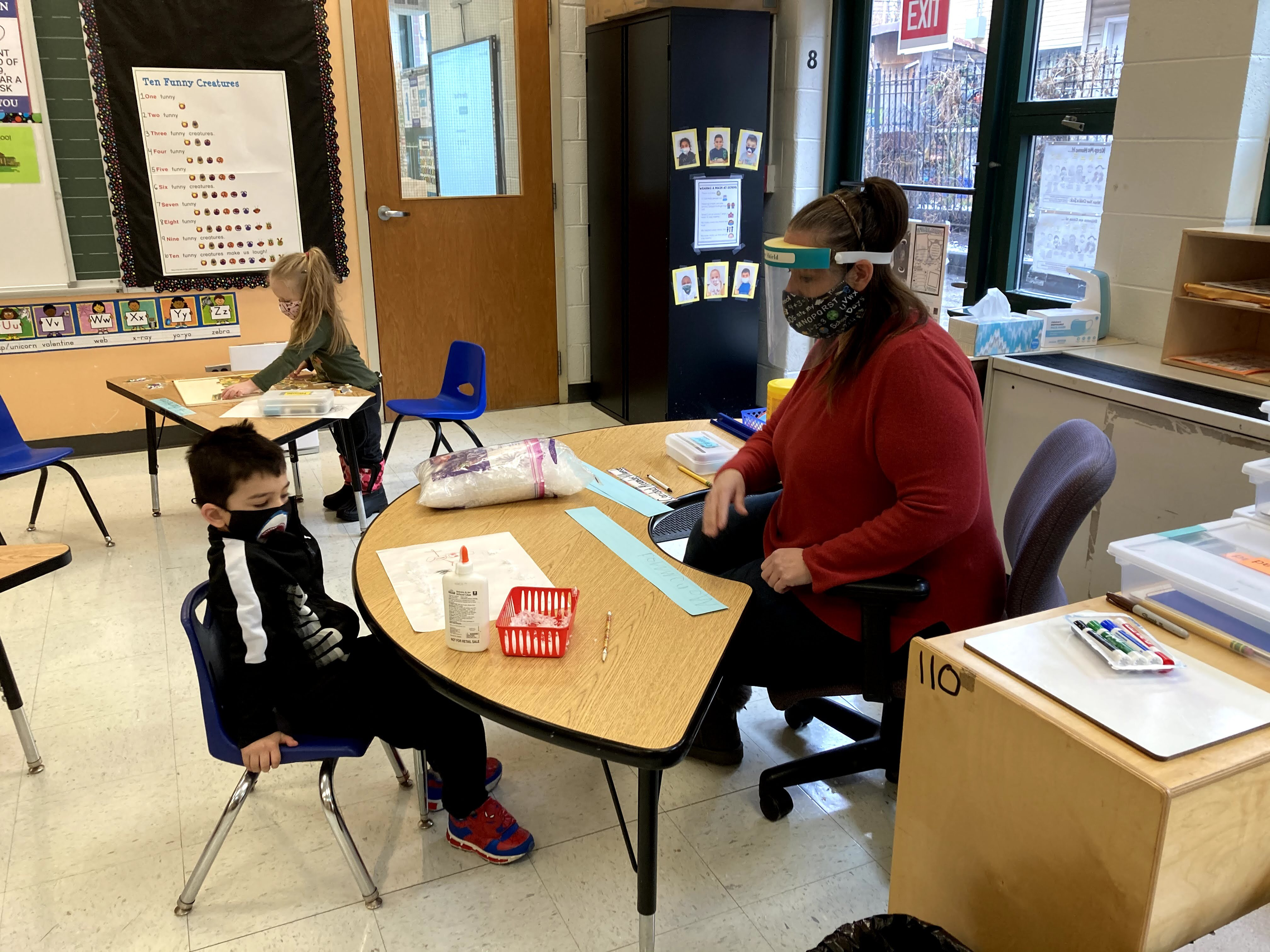 A teacher sits across a desk from a student in a classroom. Both are wearing masks.