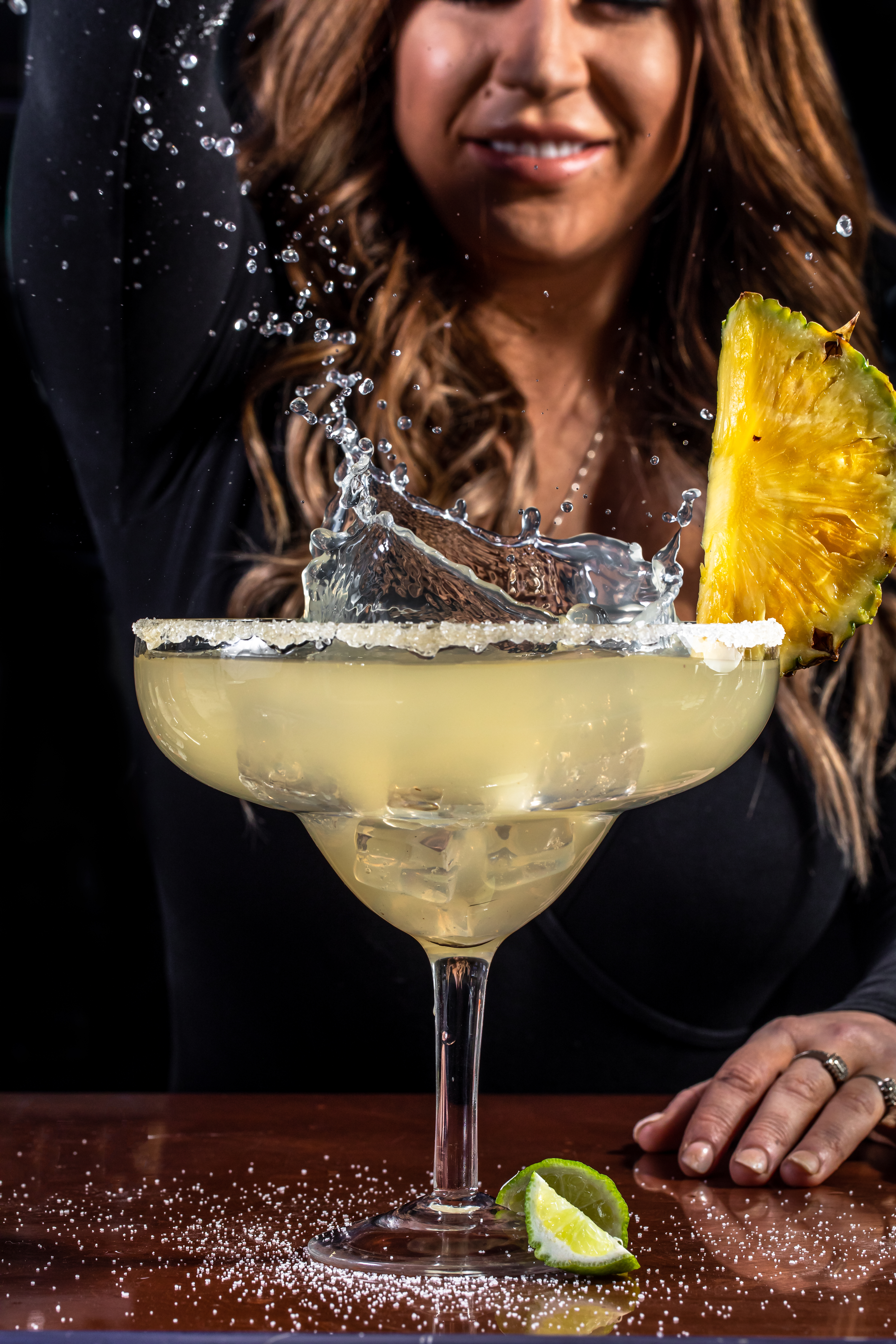 A smiling woman drops an ice cube into a large margarita glass with a pineapple wedge garnish. As the cube hits the the margarita it dramatically splashes out