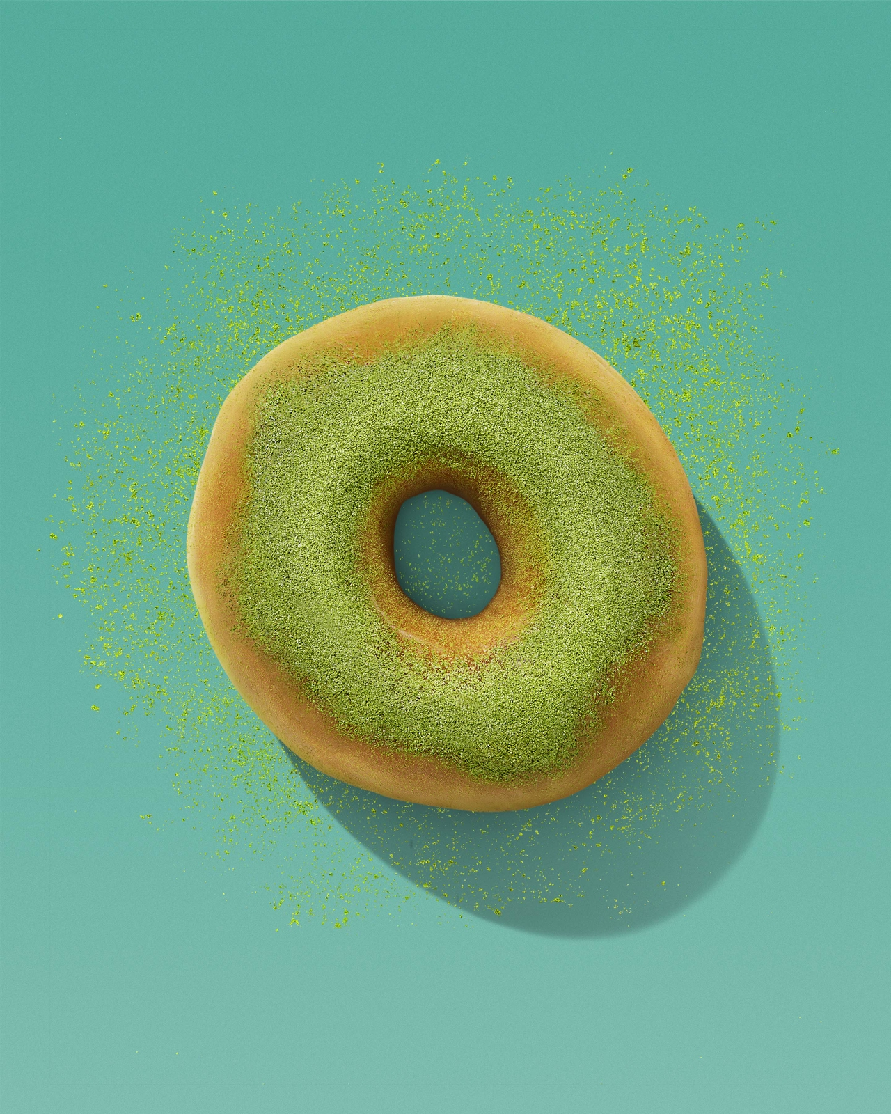 A glazed doughnut from Dunkin', topped with bright green matcha powder