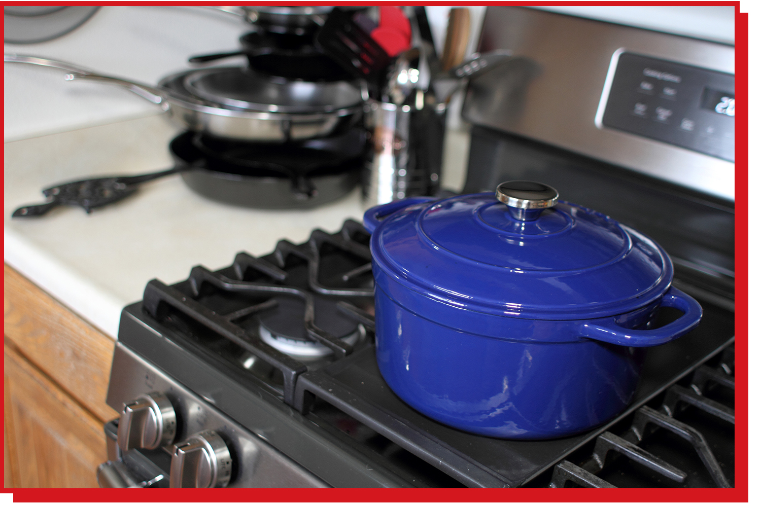 A blue Dutch oven with lid sitting on top of a stove.
